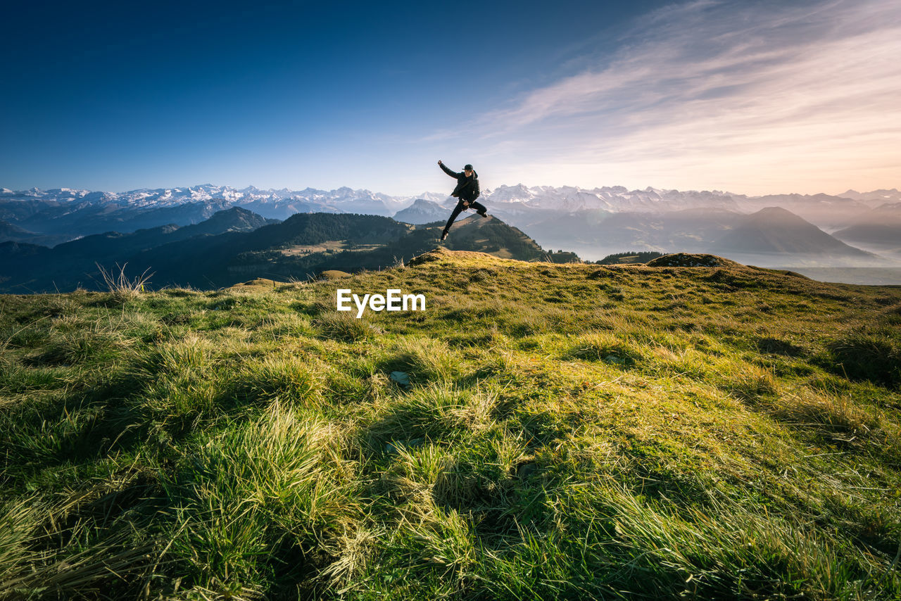 Man Jumping On Mountain Against Sky