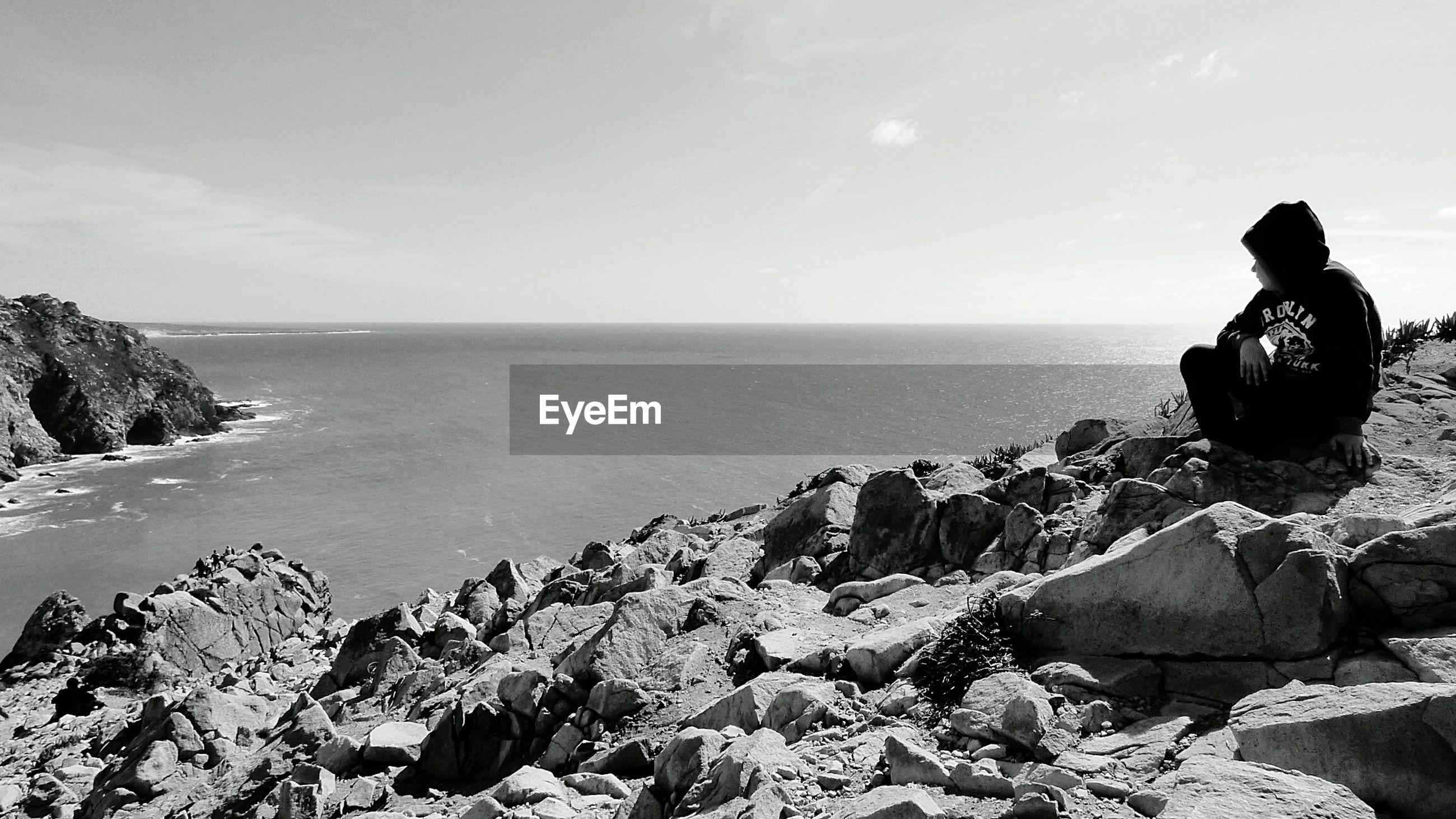 Boy sitting on cliff by sea against sky