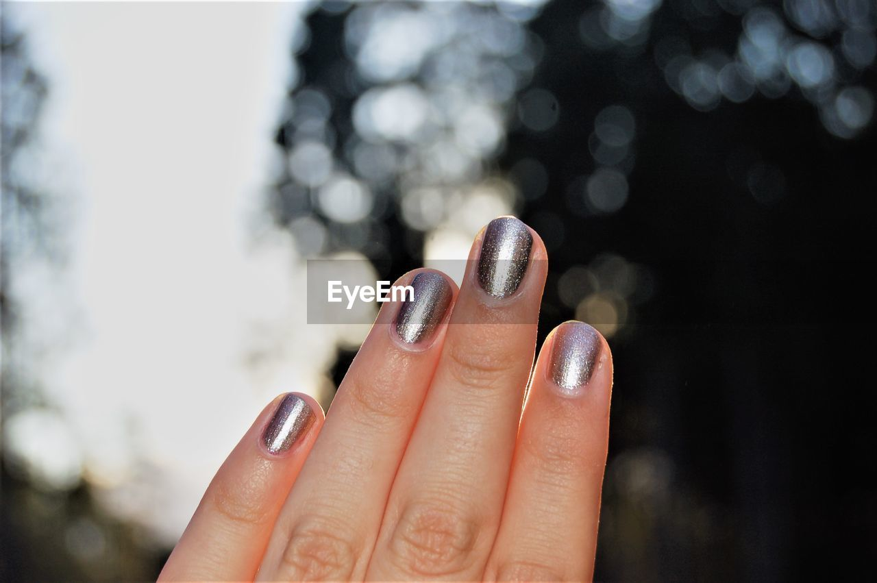 Cropped Hand Of Woman With Painted Nails Against Tree