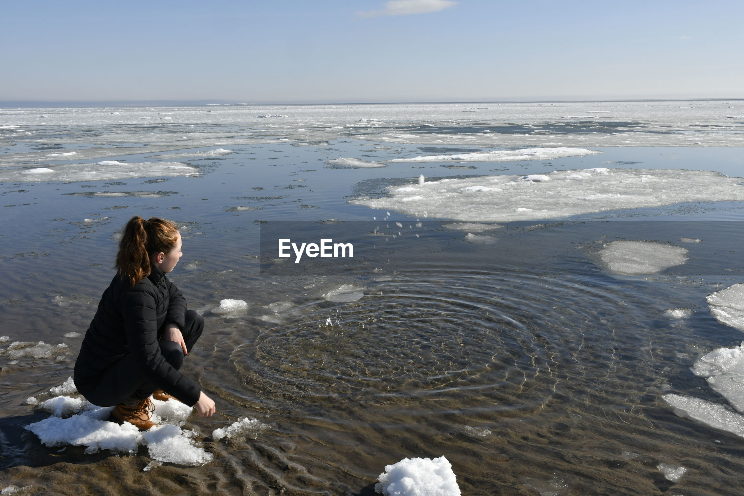 Full length of young woman sitting by frozen lake during winter