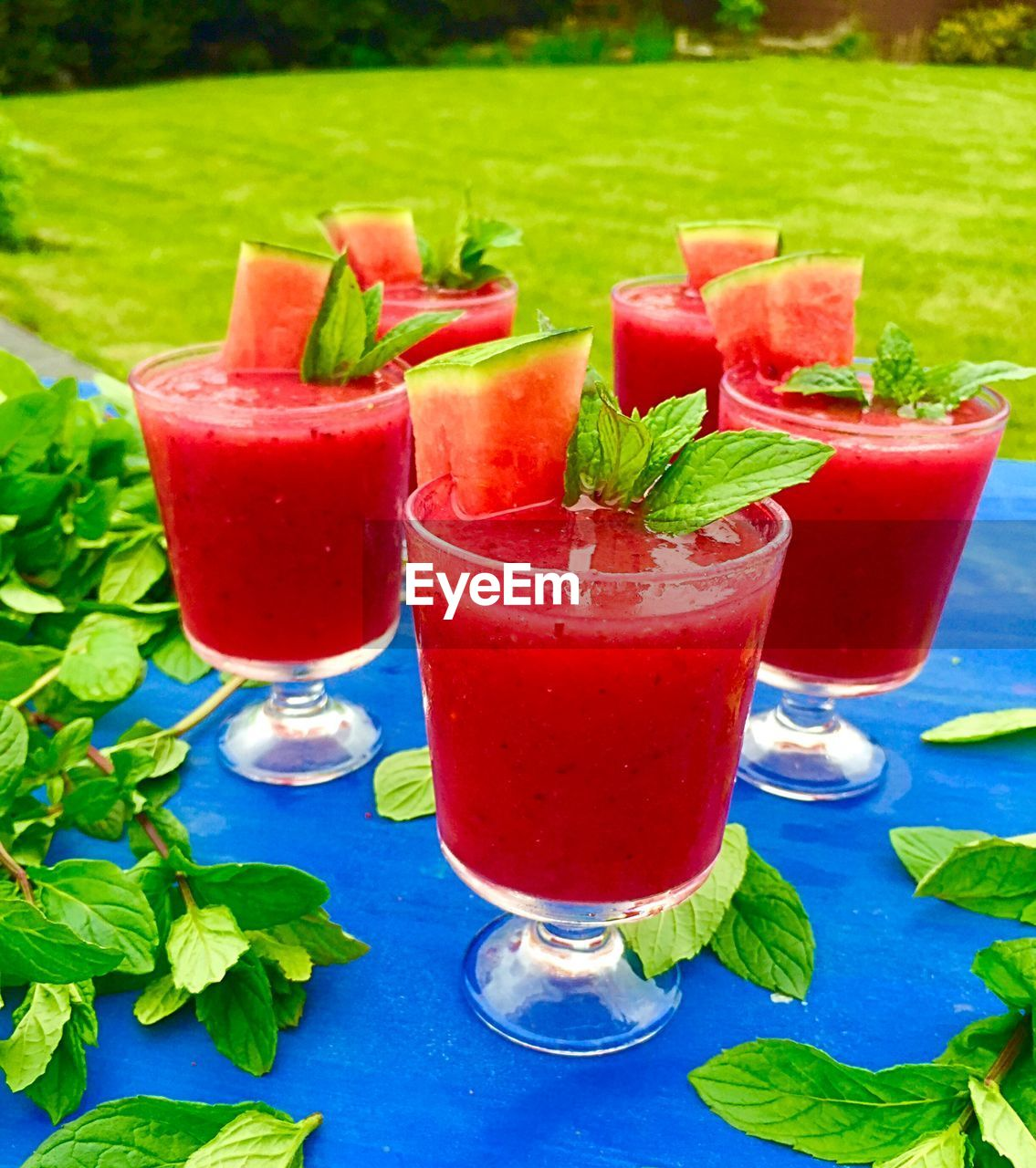 High Angle View Of Watermelon Juice With Basil Served On Table