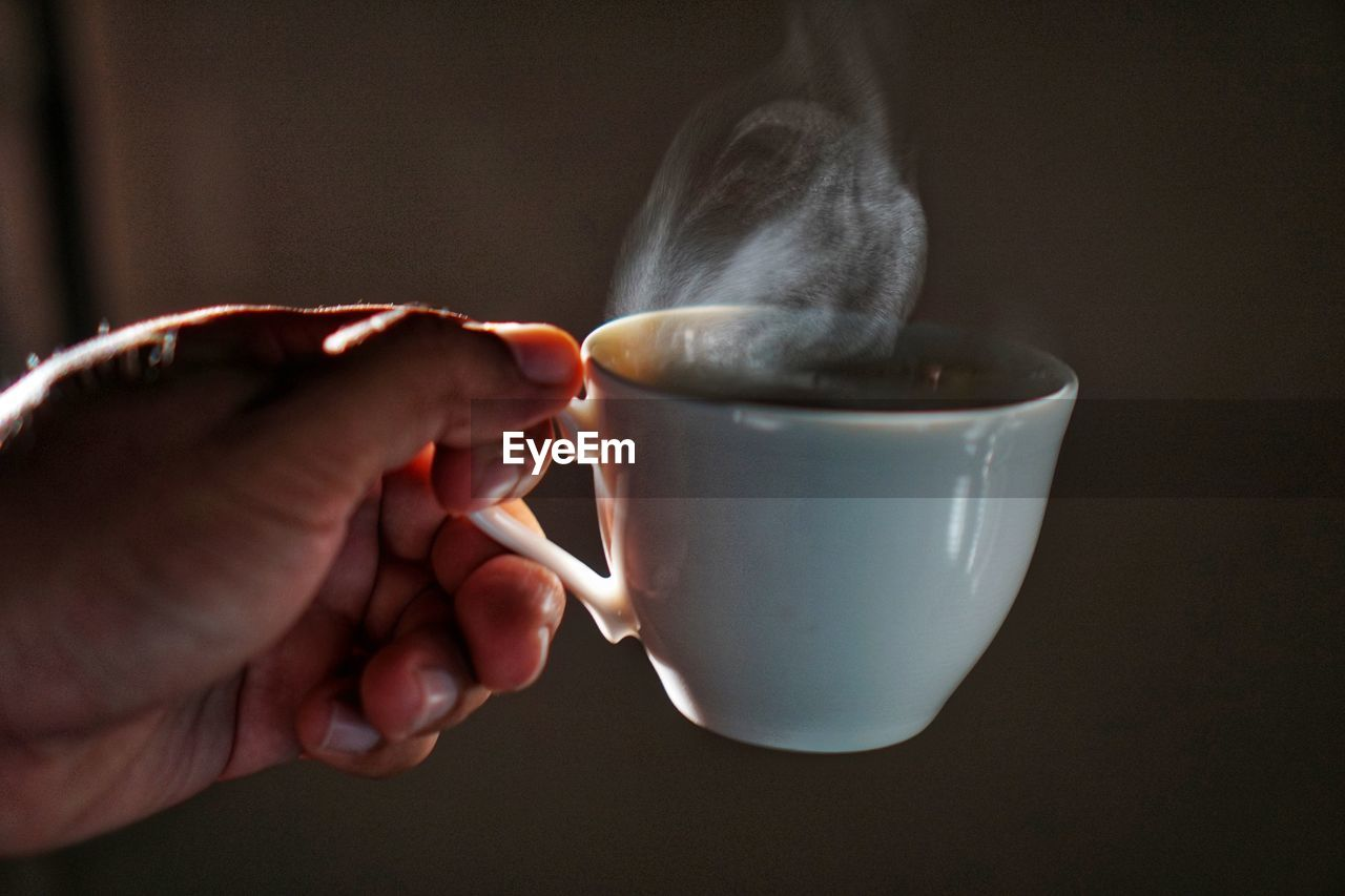 human hand, hand, cup, mug, holding, drink, one person, refreshment, human body part, food and drink, real people, coffee cup, indoors, coffee, coffee - drink, lifestyles, focus on foreground, body part, close-up, hot drink, finger, human limb, tea cup