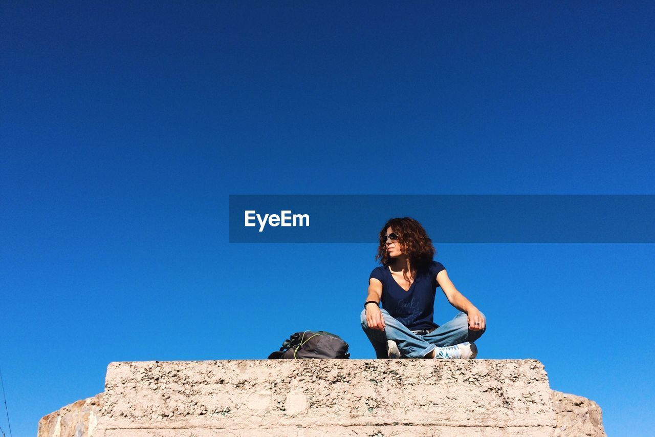 Low angle view of woman sitting on rock against clear blue sky