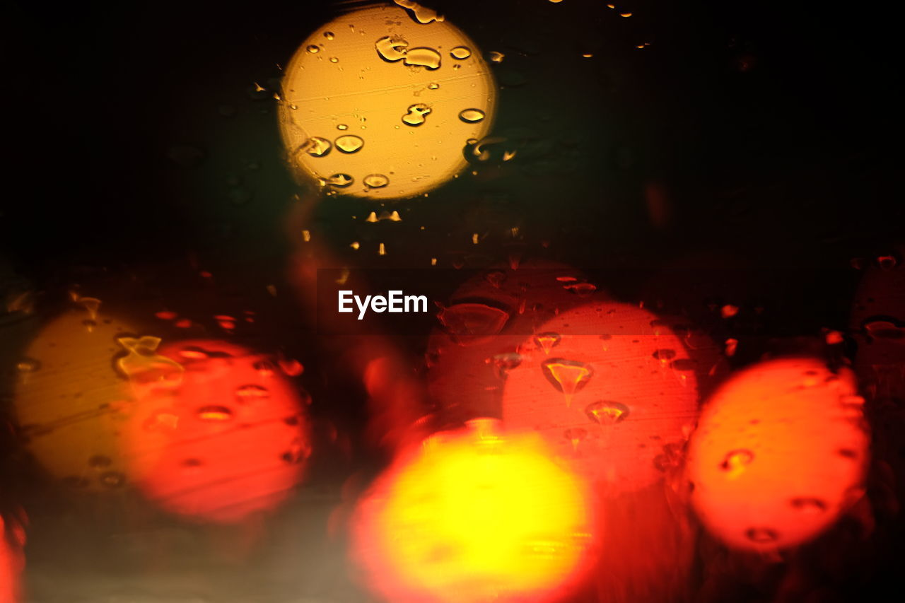 drop, close-up, wet, water, no people, indoors, transparent, orange color, glass - material, selective focus, illuminated, red, window, vehicle interior, rain, bubble, multi colored, lighting equipment, nature, raindrop, purity