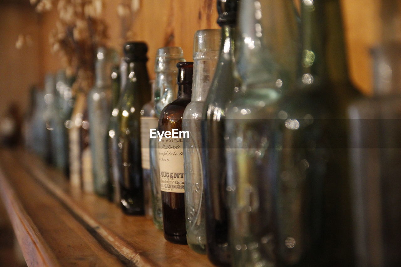 container, bottle, indoors, in a row, food and drink, alcohol, refreshment, glass - material, drink, no people, wine bottle, transparent, selective focus, still life, focus on foreground, close-up, arrangement, wine, table, large group of objects