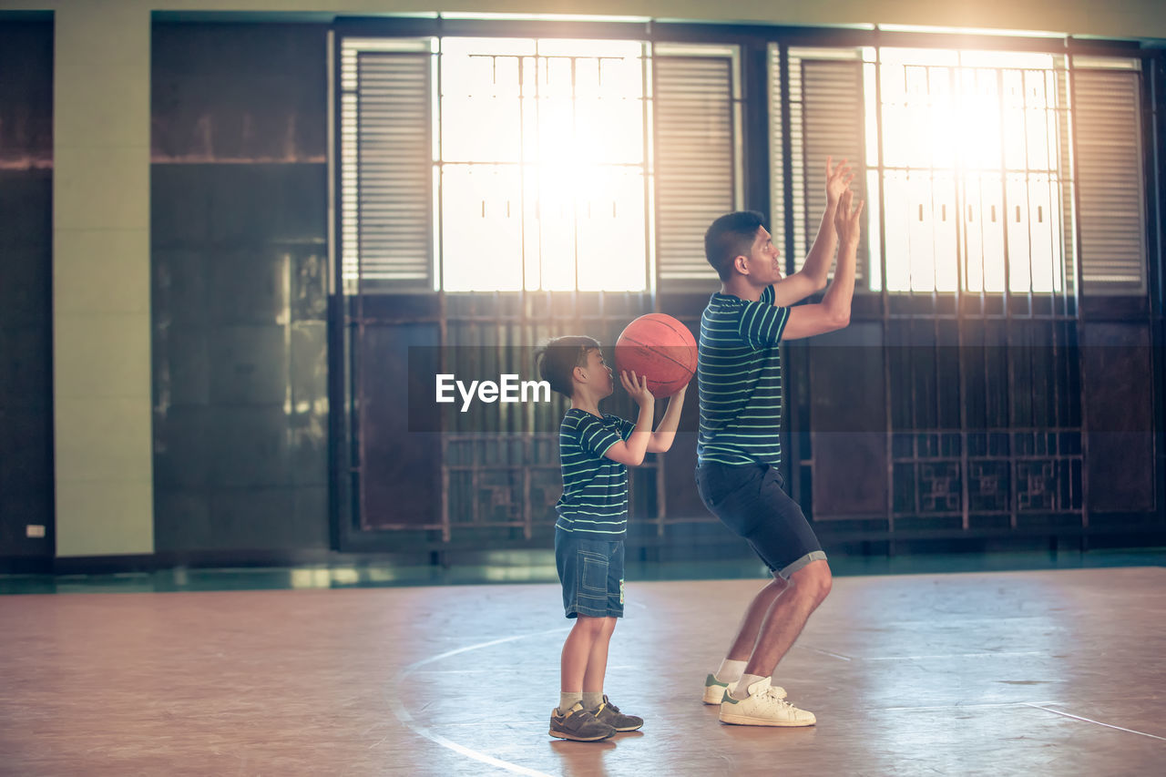 Father teaching son basketball