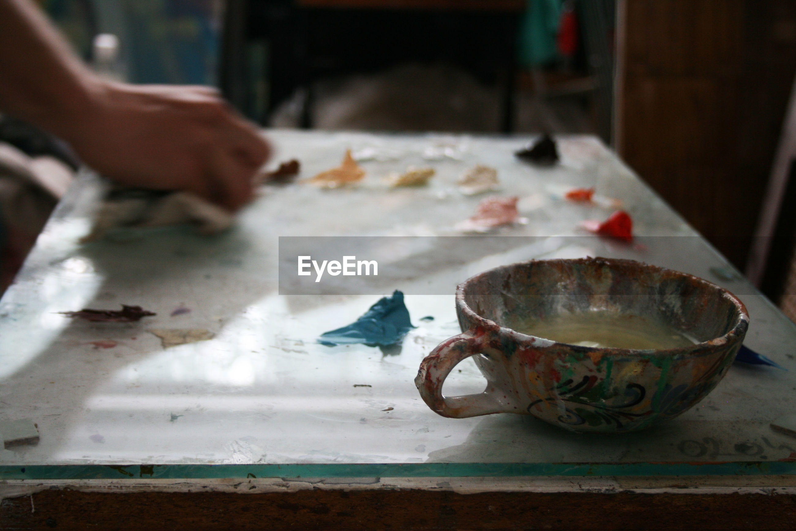 Cropped hand of painter working in studio with focus on cup