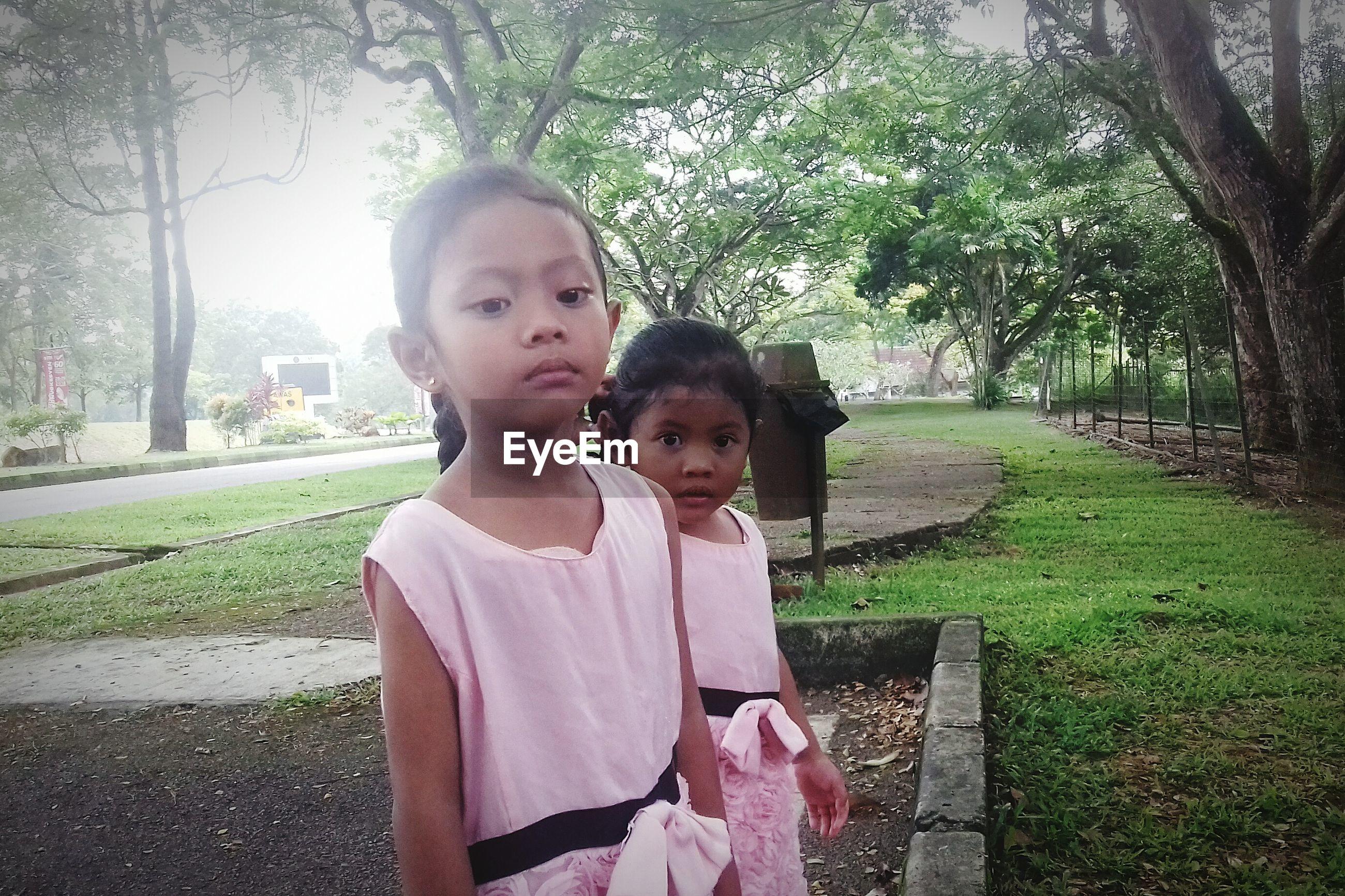 Portrait of siblings standing in park
