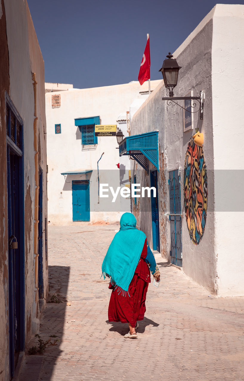 architecture, building exterior, built structure, building, real people, full length, rear view, day, one person, sunlight, nature, flag, walking, clothing, women, traditional clothing, residential district, men, lifestyles, outdoors, alley