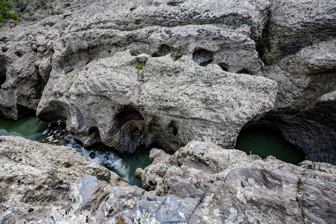 rock, rock - object, rock formation, solid, no people, nature, water, day, rough, textured, geology, outdoors, tranquility, land, beauty in nature, physical geography, high angle view, river, motion, eroded, formation