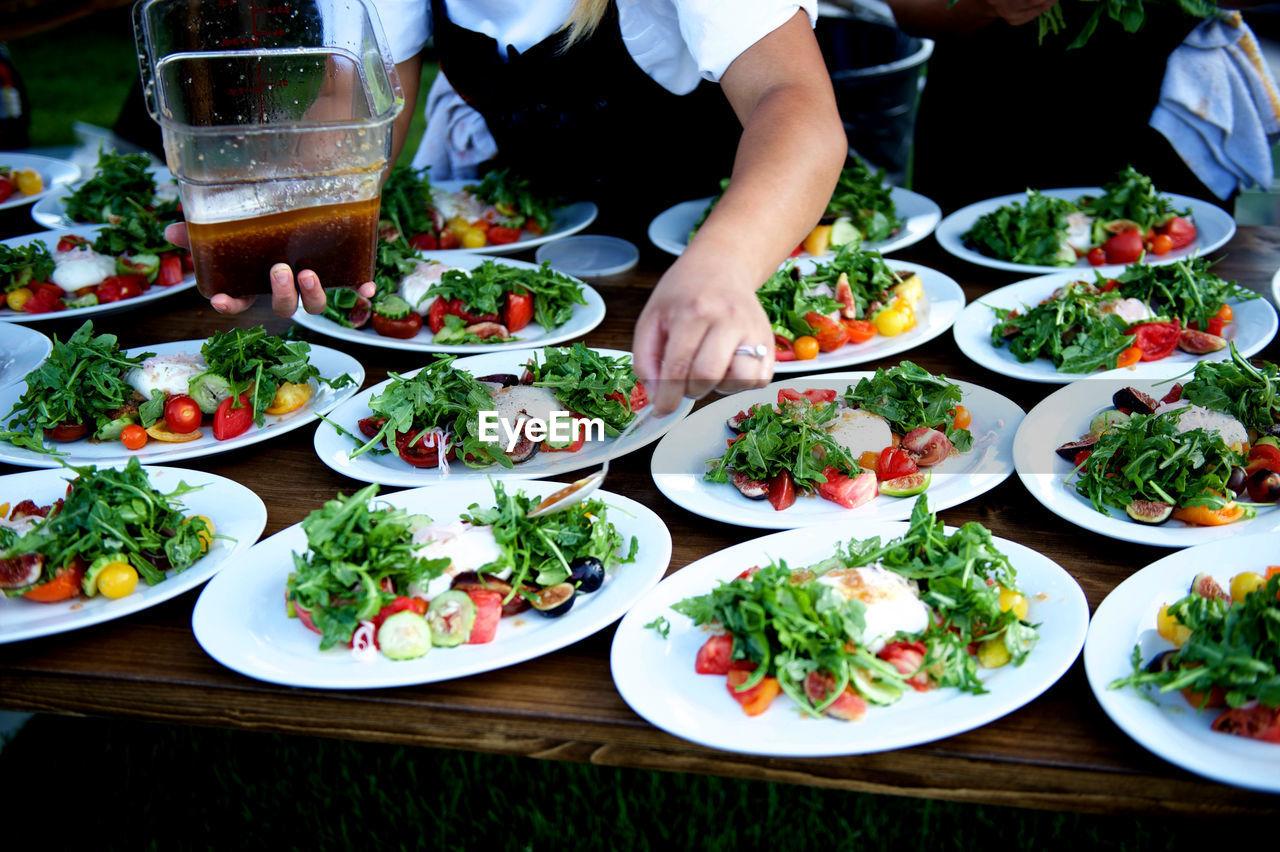 Midsection Of Waitress Preparing Salad