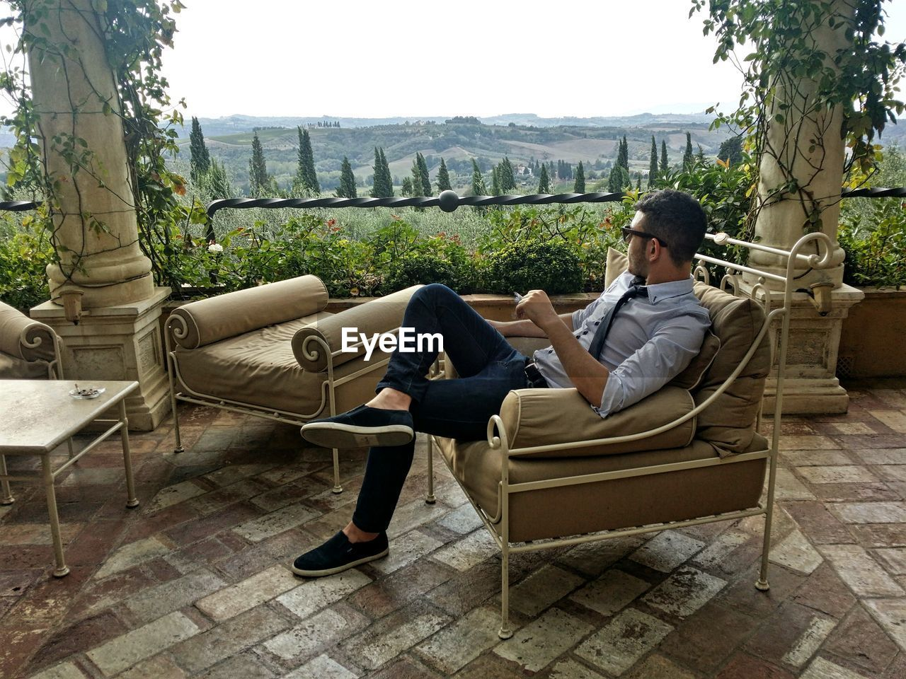 Man sitting on chair at yard against sky