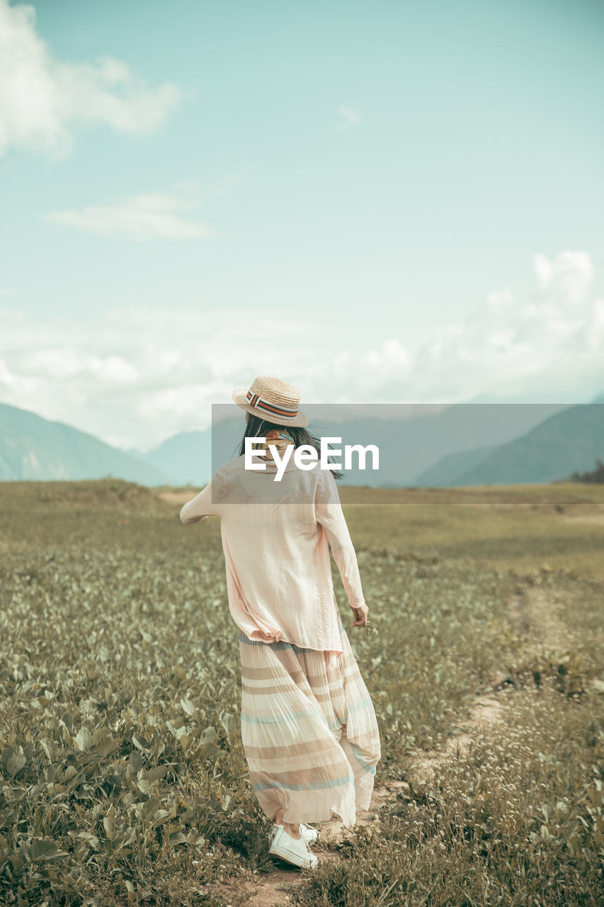 Rear View Of Woman Walking On Footpath Amidst Field Against Sky