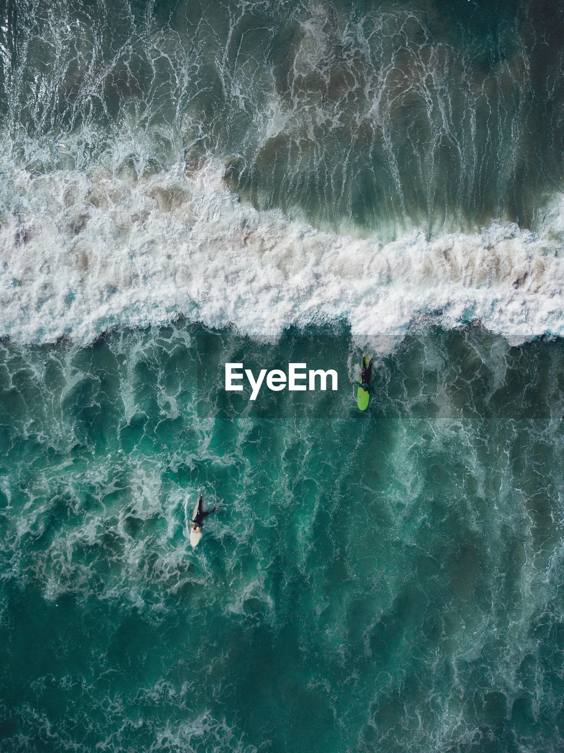 Aerial view of men surfing on sea