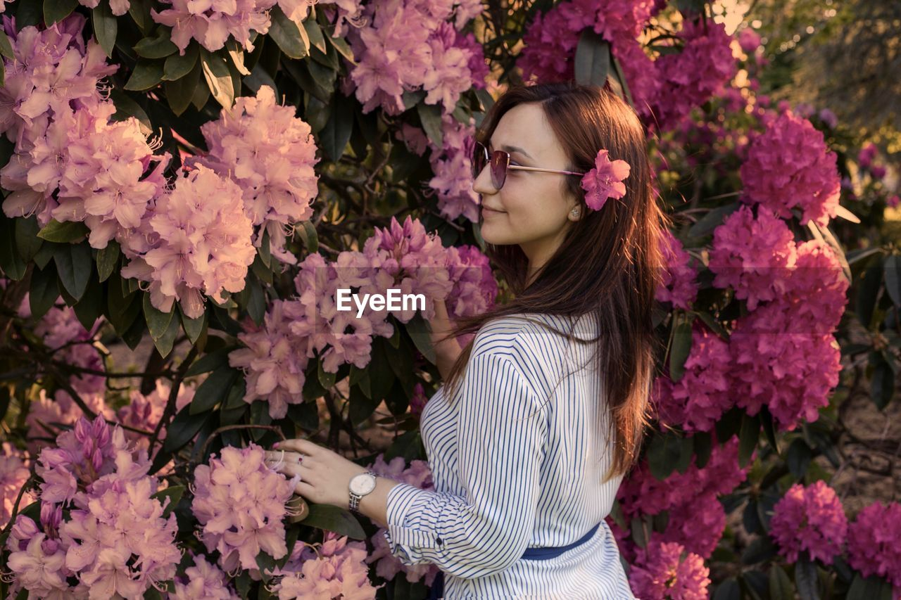 Woman in sunglasses standing by pink flowering plants