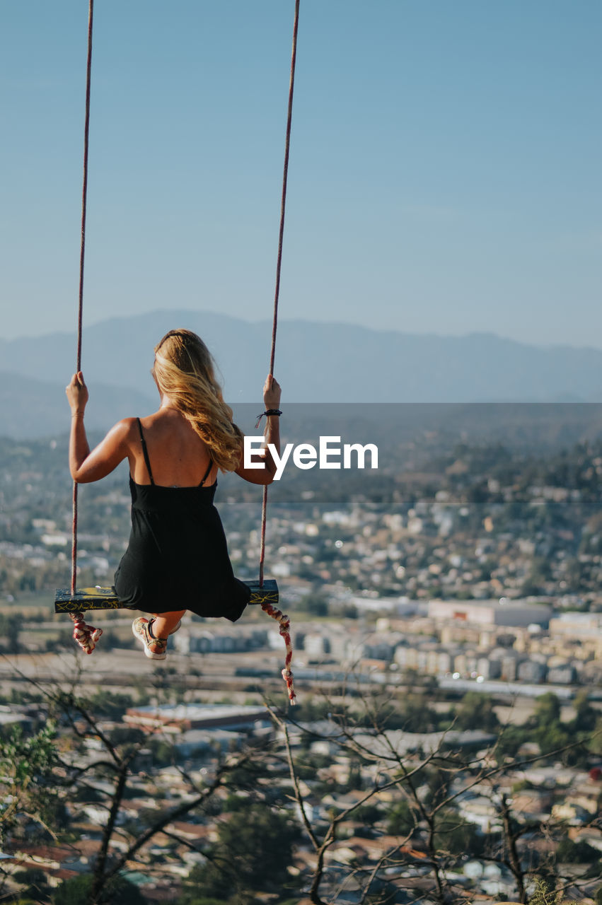 Rear View Of Woman On Swing Against Clear Sky