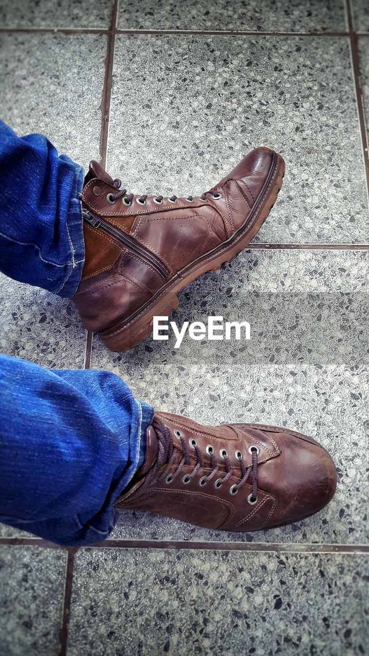 shoe, low section, human leg, real people, human foot, human body part, men, standing, one person, lifestyles, high angle view, street, brown, day, pair, outdoors, close-up, people