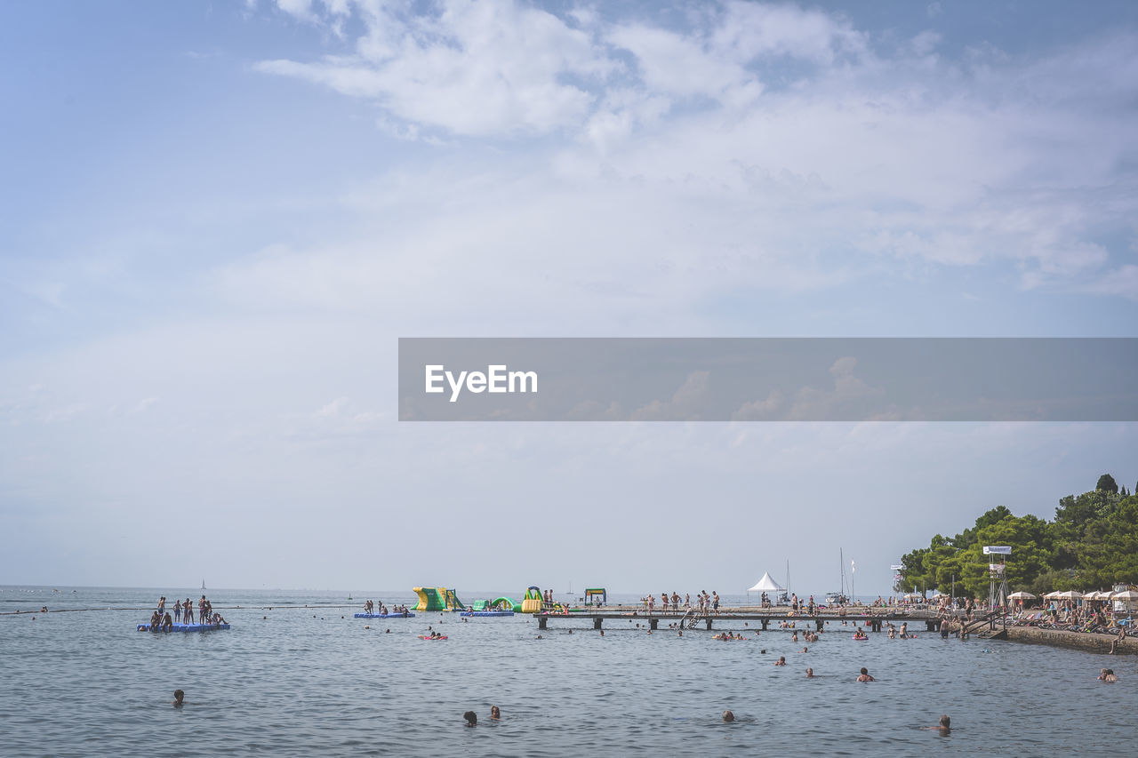 water, sky, sea, nautical vessel, cloud - sky, group of people, transportation, waterfront, nature, day, beauty in nature, real people, crowd, mode of transportation, large group of people, beach, land, lifestyles, scenics - nature, outdoors