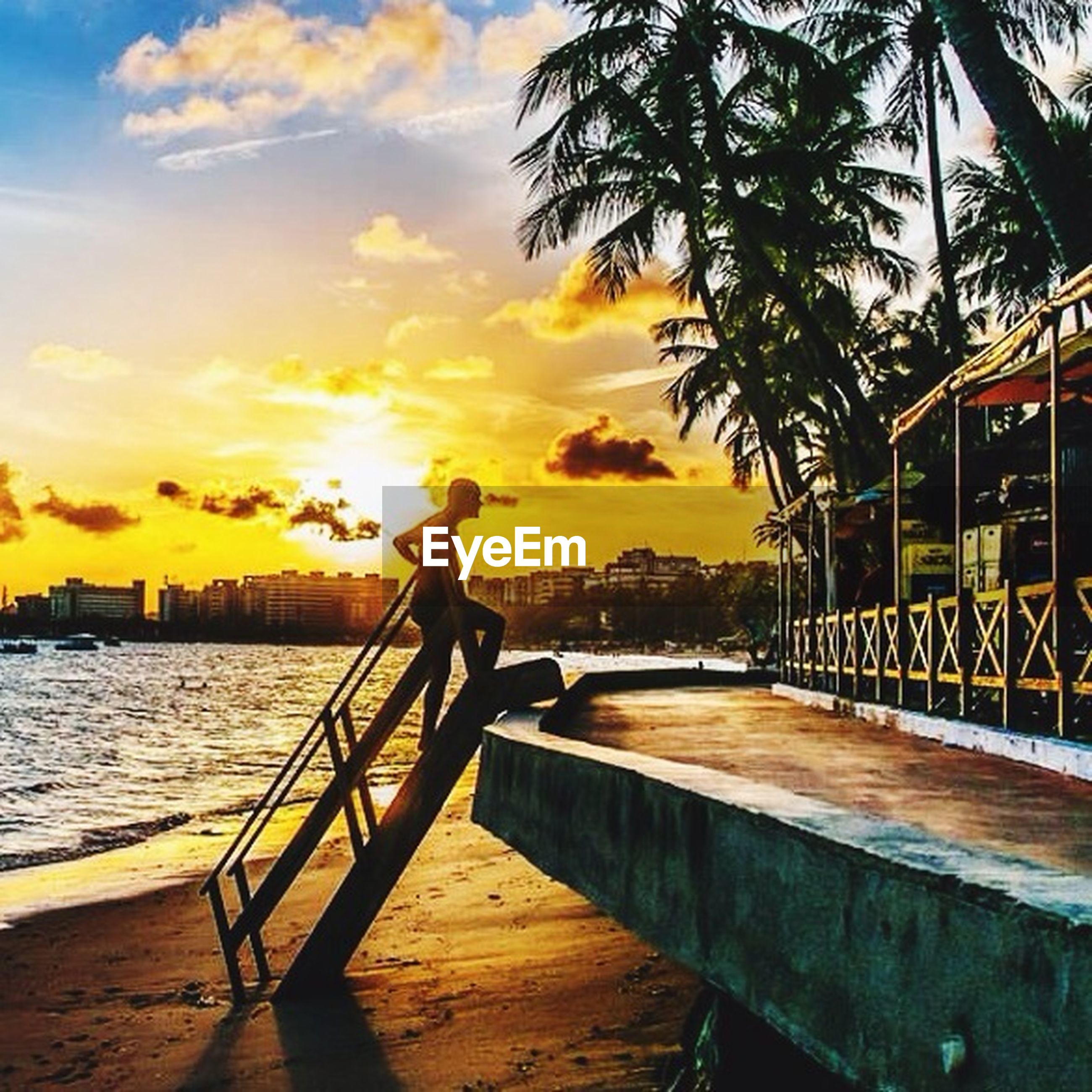 sunset, water, sky, sea, railing, orange color, pier, scenics, tranquility, beauty in nature, silhouette, tranquil scene, nature, cloud - sky, bench, tree, idyllic, horizon over water