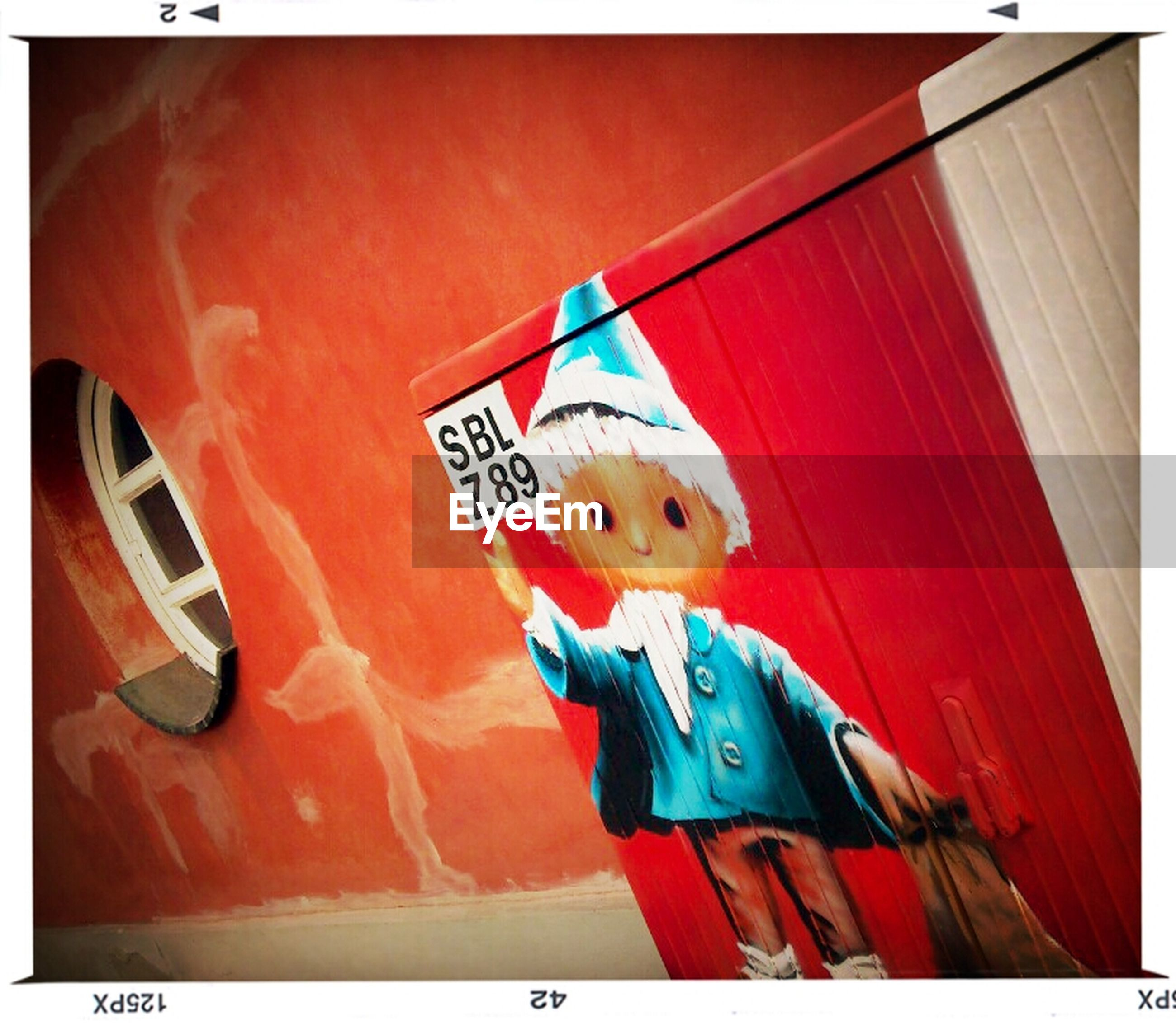 transfer print, auto post production filter, red, human representation, text, western script, art, art and craft, animal representation, creativity, communication, toy, low angle view, wall - building feature, sign, day, no people, outdoors, multi colored