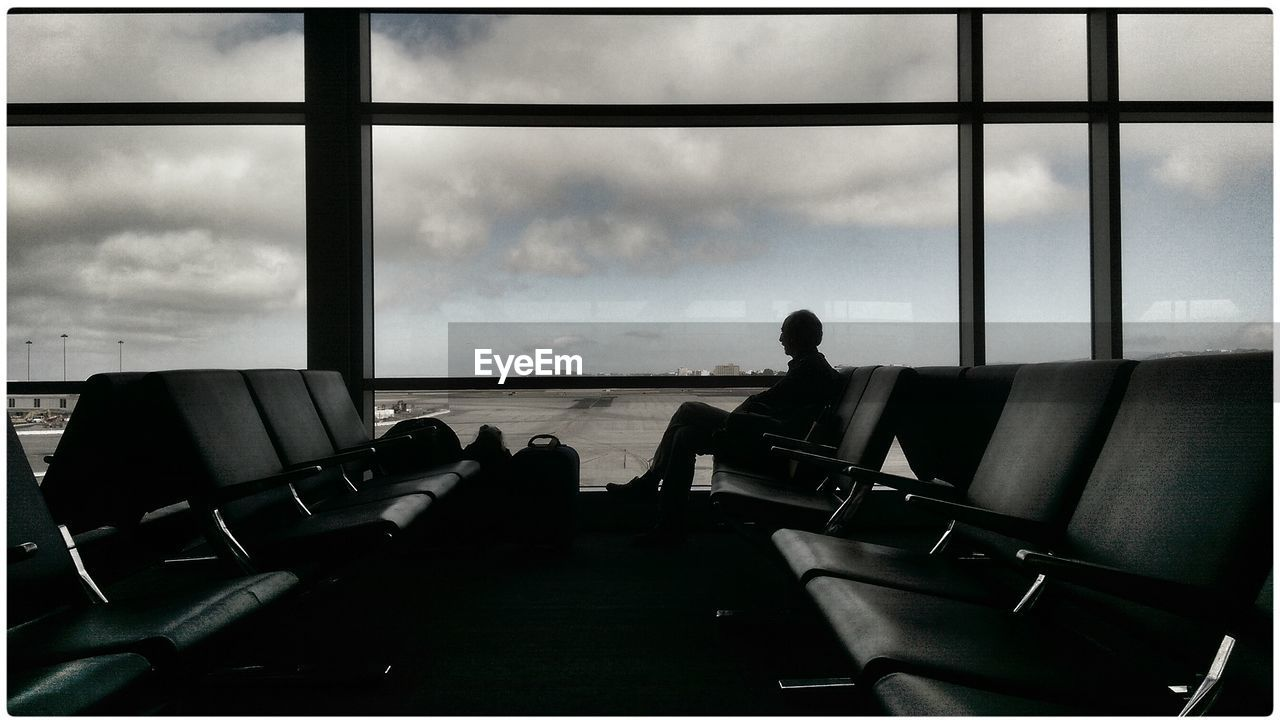 Silhouette of person in airport waiting for flight