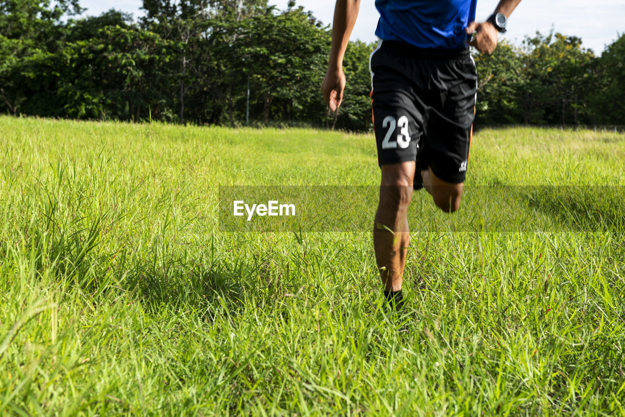 plant, grass, one person, motion, running, nature, field, day, land, green color, low section, real people, casual clothing, on the move, rear view, growth, lifestyles, child, walking, outdoors, shorts