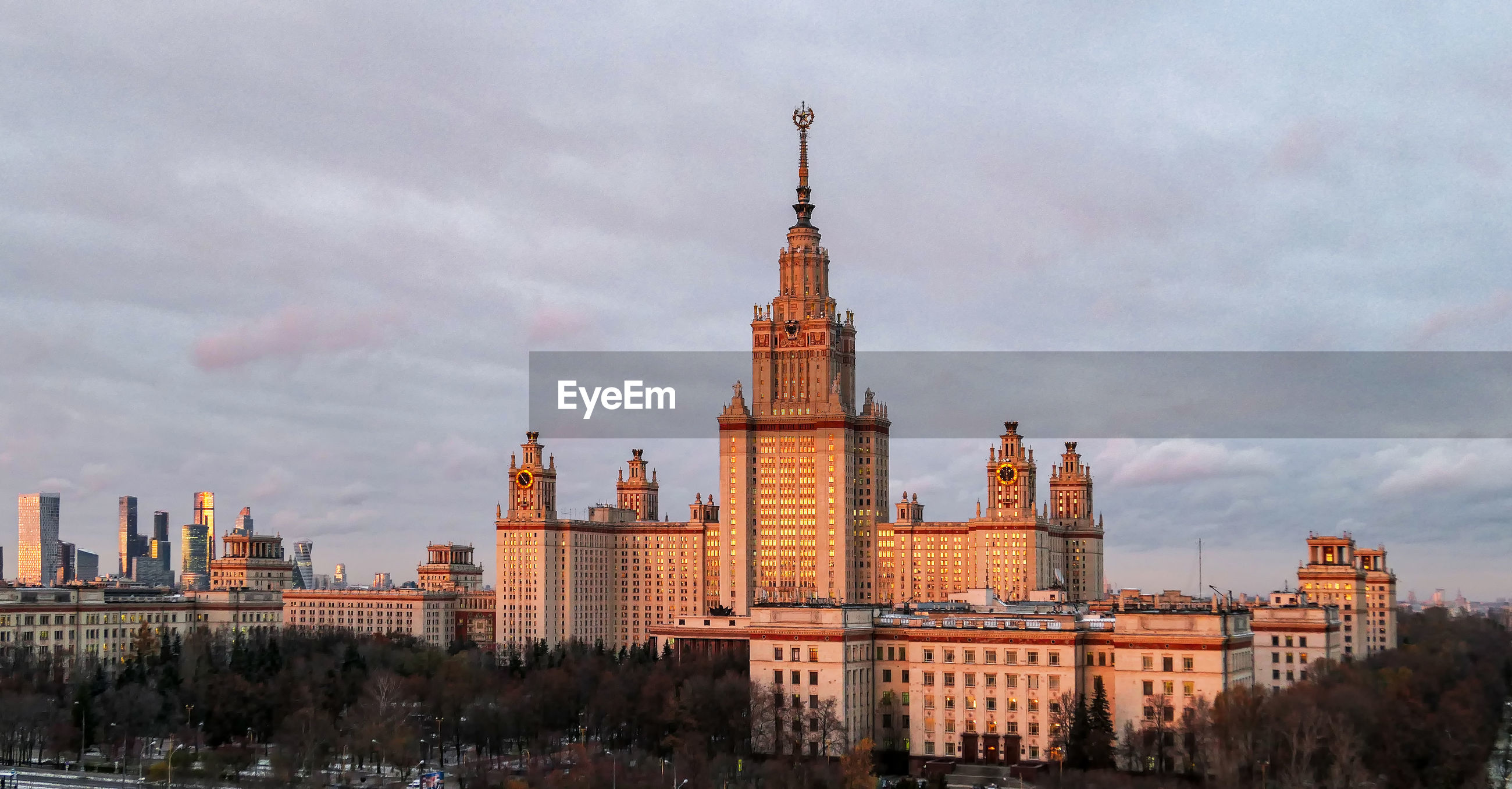 Aerial panoramic view of sunset reflection in windows of moscow university under dramatic cloudy sky