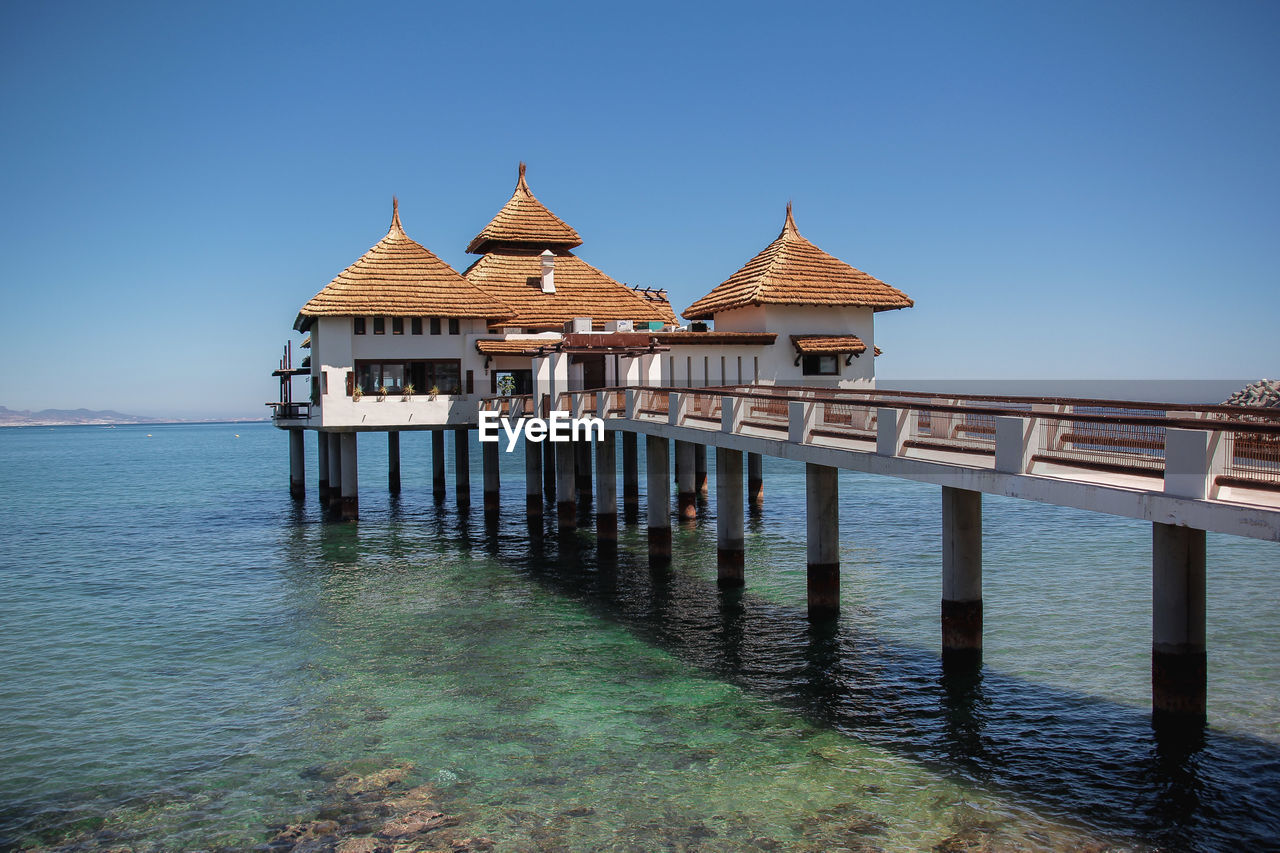 water, sky, architecture, built structure, sea, clear sky, building exterior, nature, blue, religion, waterfront, no people, building, belief, travel destinations, place of worship, travel, spirituality, day, wooden post