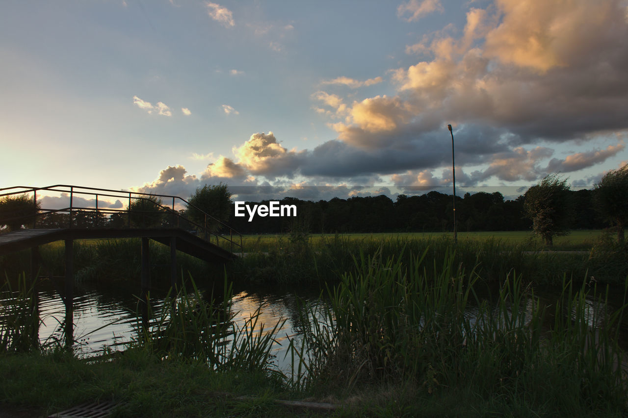 sky, cloud - sky, water, nature, river, outdoors, connection, scenics, bridge - man made structure, tranquil scene, no people, reflection, sunset, tranquility, beauty in nature, tree, grass, travel destinations, day