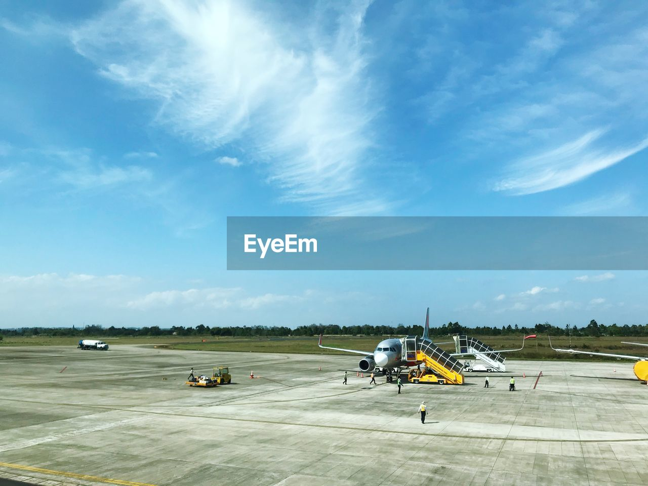 air vehicle, airport, airport runway, airplane, mode of transportation, transportation, sky, cloud - sky, travel, runway, nature, day, land vehicle, sunlight, public transportation, no people, commercial airplane, road, aerospace industry, journey, outdoors