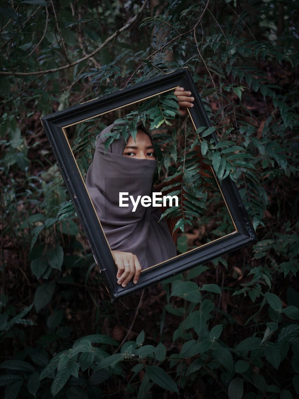 Portrait of woman wearing hijab holding picture frame against plants