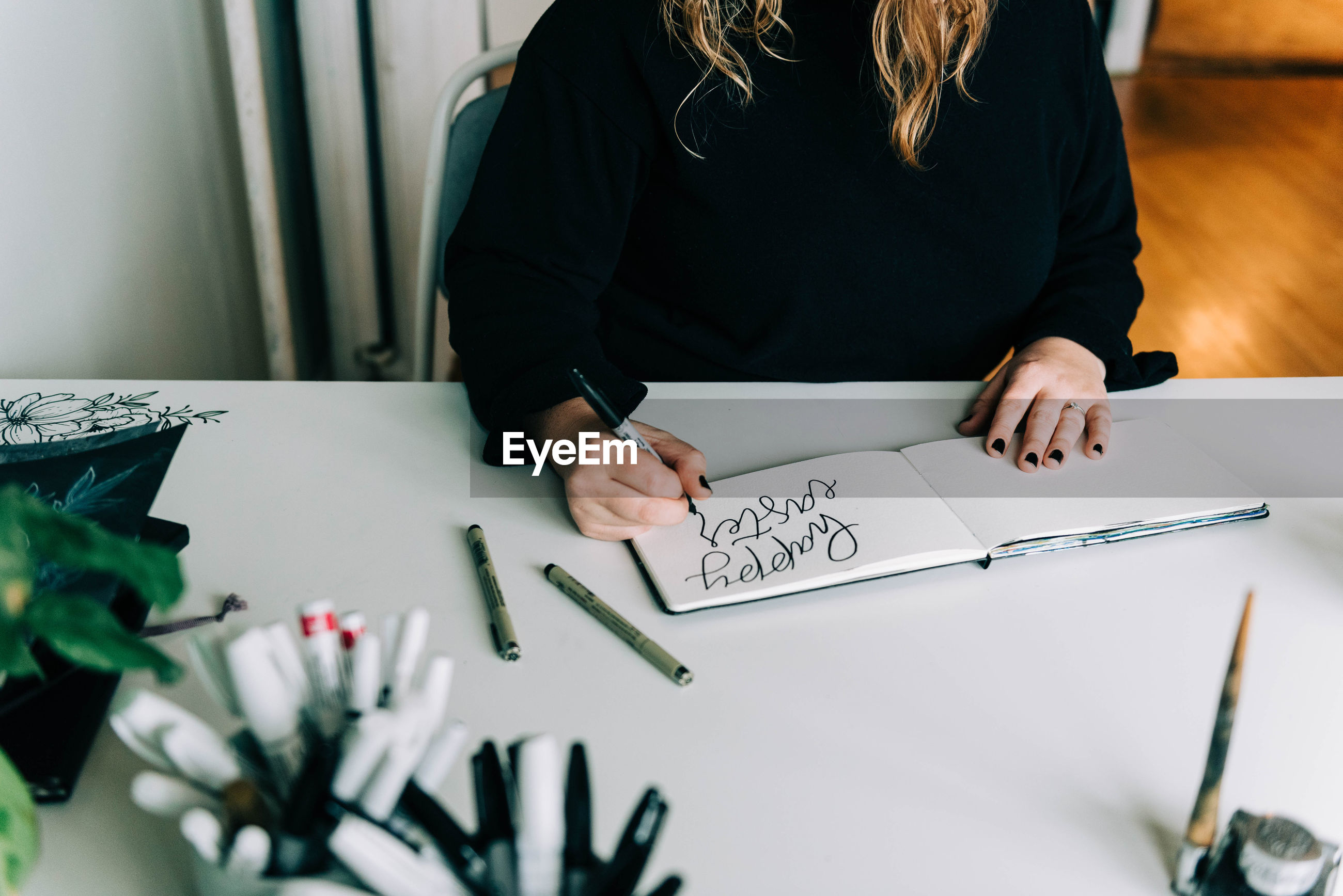 MIDSECTION OF WOMAN WITH TEXT ON TABLE