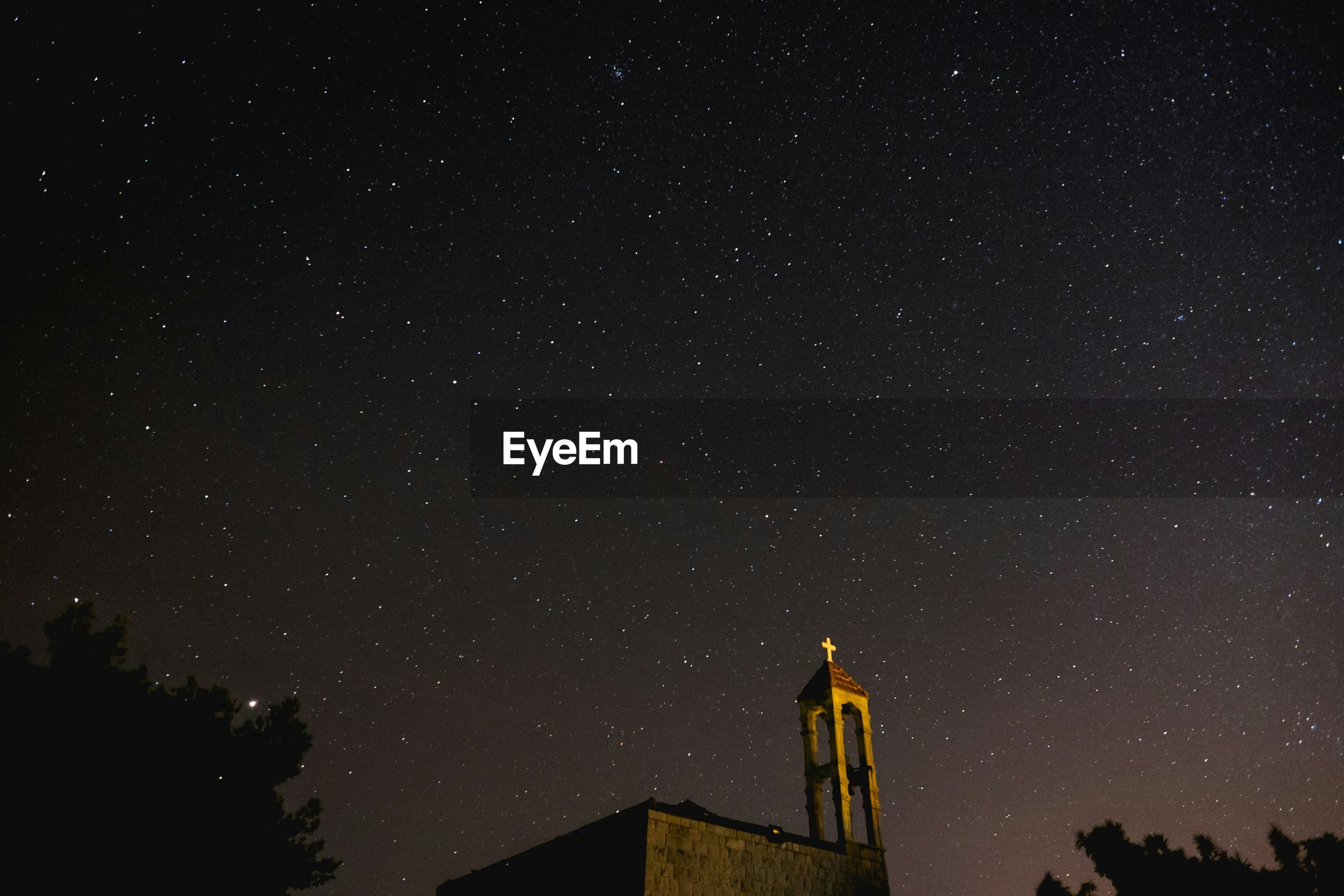 Low angle view of church against star field at night