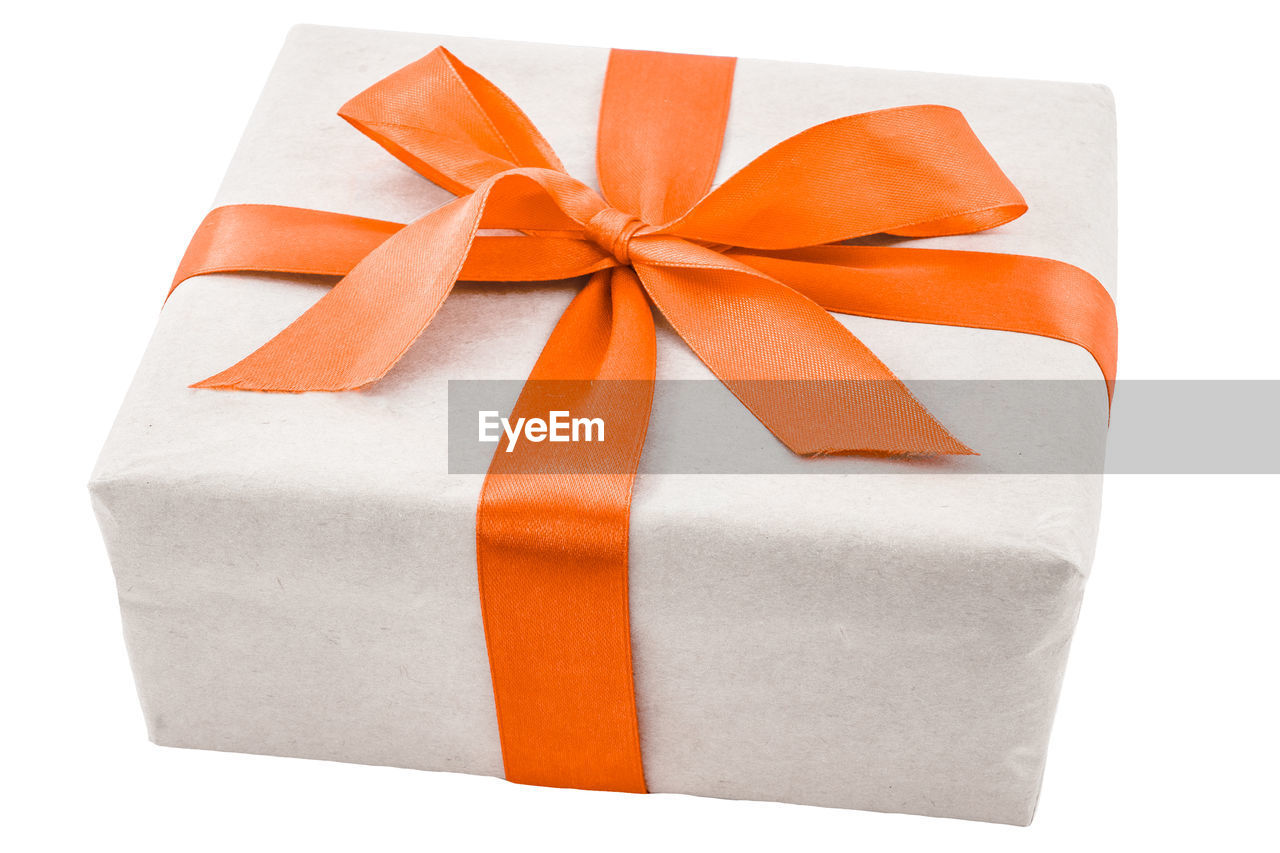 ribbon, gift, studio shot, bow, ribbon - sewing item, tied bow, celebration, white background, indoors, wrapped, close-up, box, box - container, surprise, still life, container, cut out, no people, paper, orange color, gift box, wrapping paper