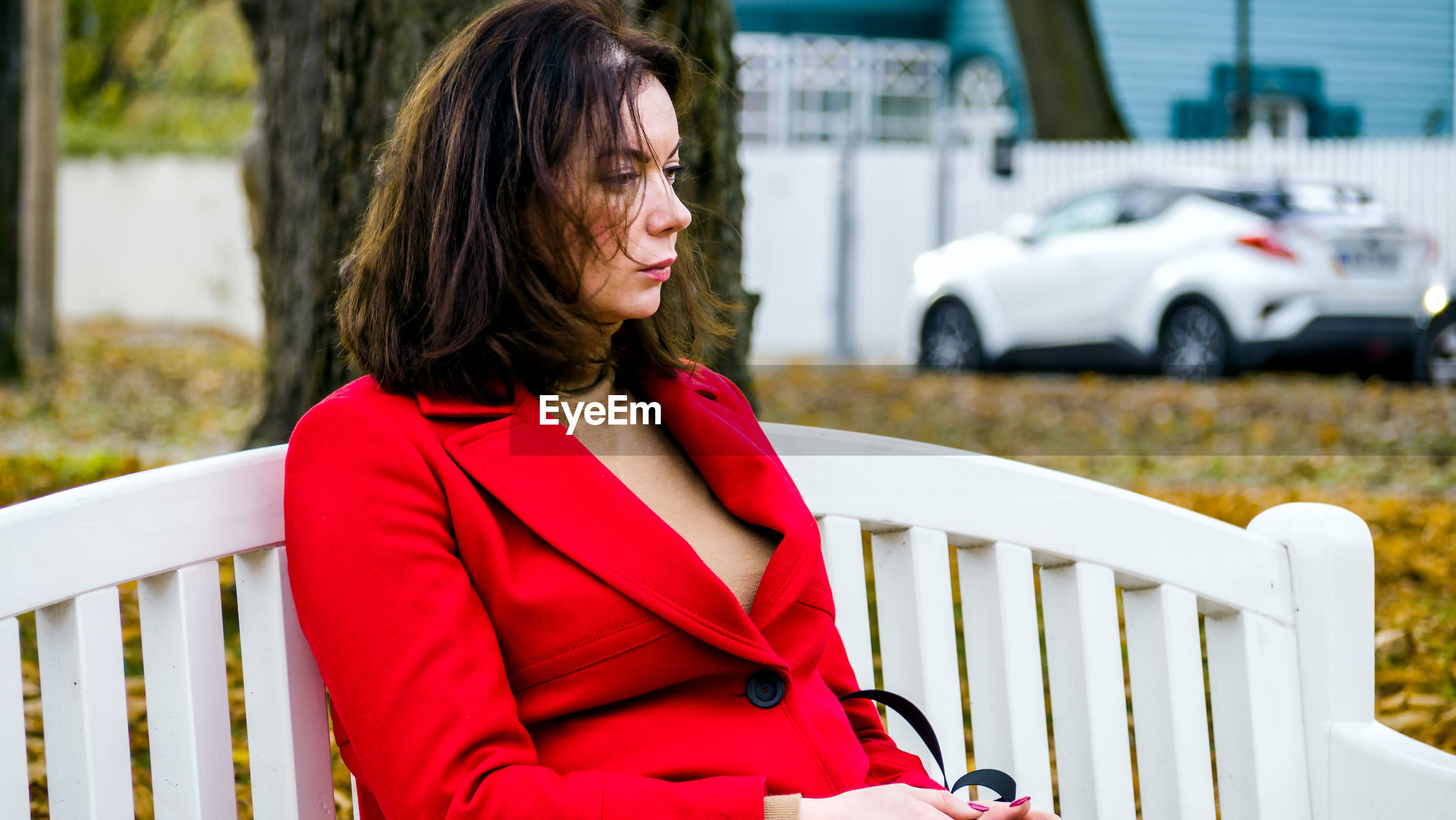 Woman looking away while sitting on bench at park
