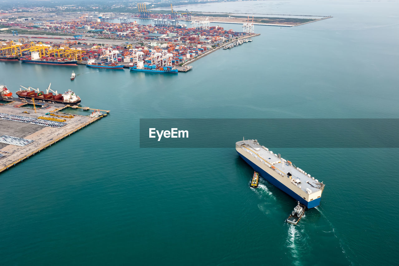 Roro ship and tugboat sailing in sea and commercial dock international container ship background