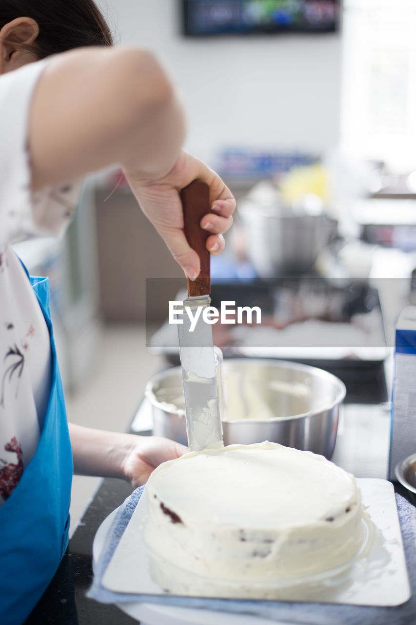 Cropped Image Of Woman Spreading Cream On Sponge Cake At Kitchen