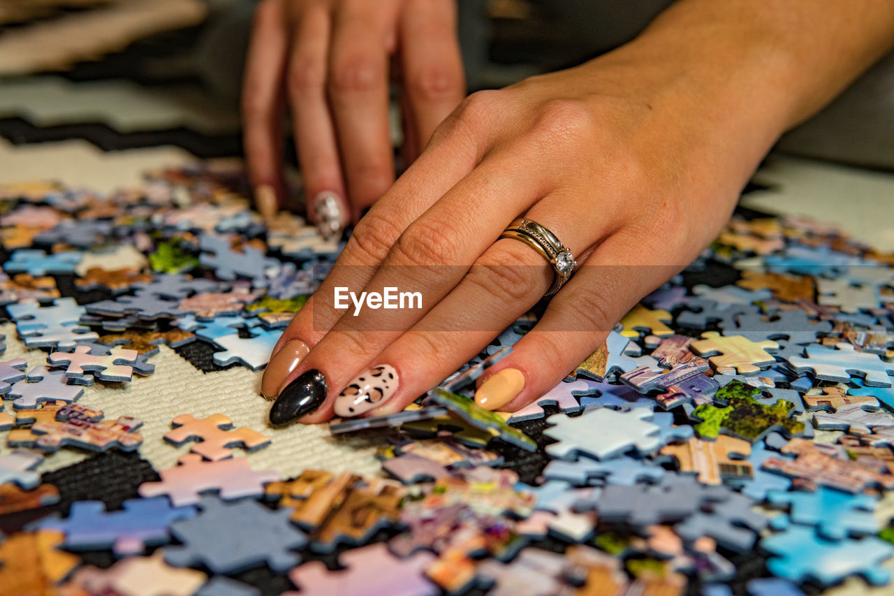 human hand, human body part, hand, jigsaw piece, puzzle, indoors, real people, table, leisure activity, people, body part, jigsaw puzzle, human finger, selective focus, finger, lifestyles, multi colored, large group of objects, close-up