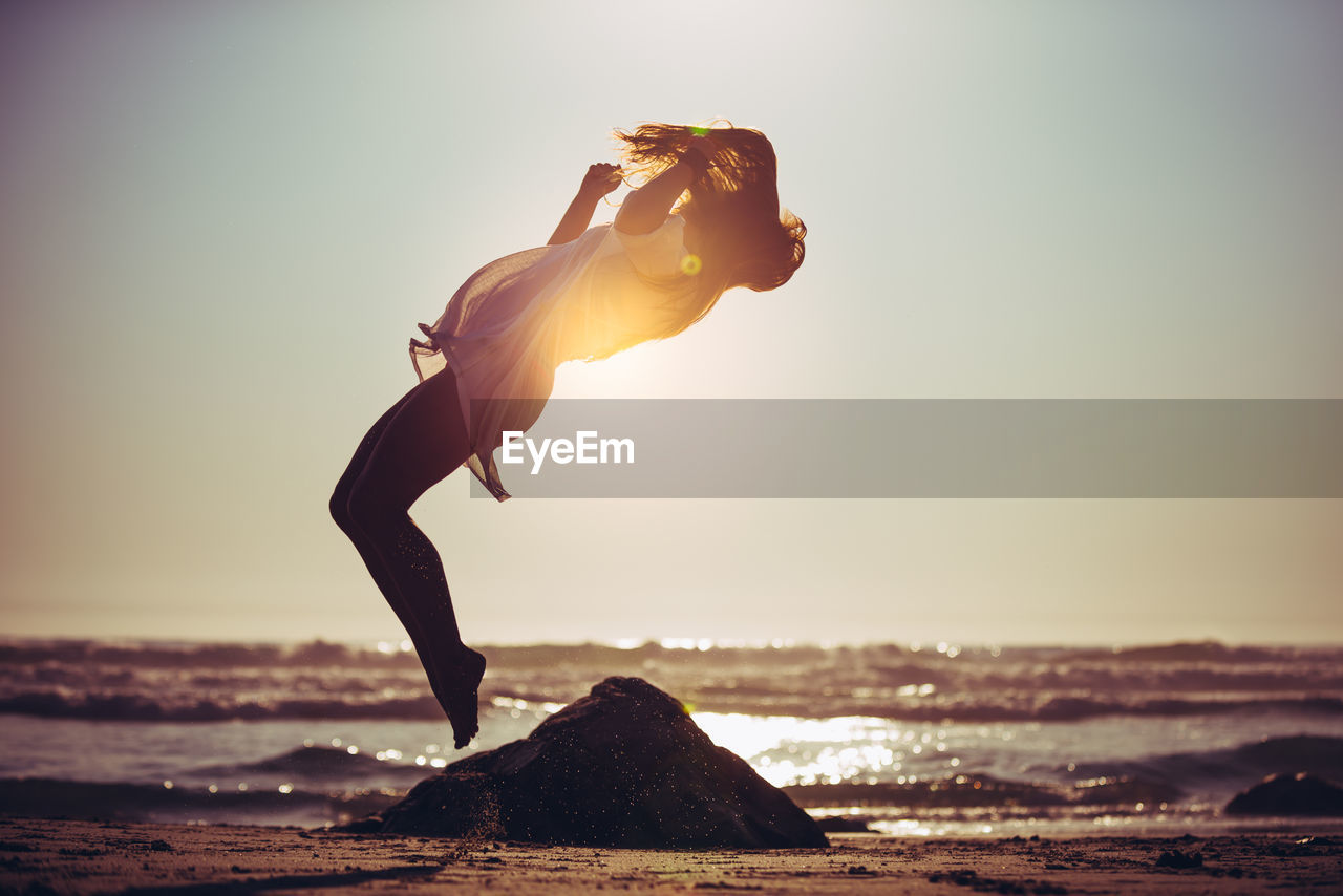 FULL LENGTH SIDE VIEW OF WOMAN JUMPING ON BEACH