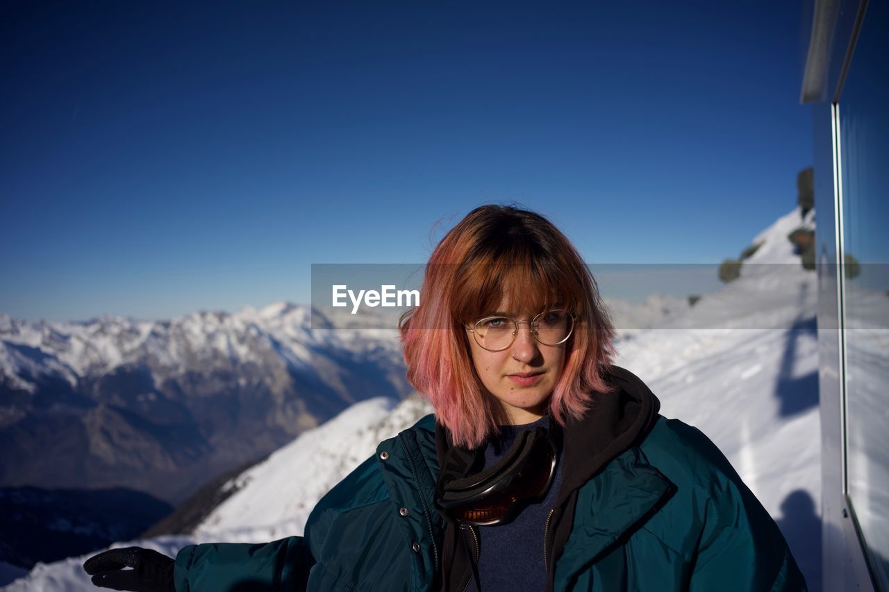 one person, winter, leisure activity, mountain, real people, lifestyles, portrait, snow, sky, headshot, cold temperature, front view, warm clothing, adult, beauty in nature, mountain range, clothing, scenics - nature, snowcapped mountain, outdoors