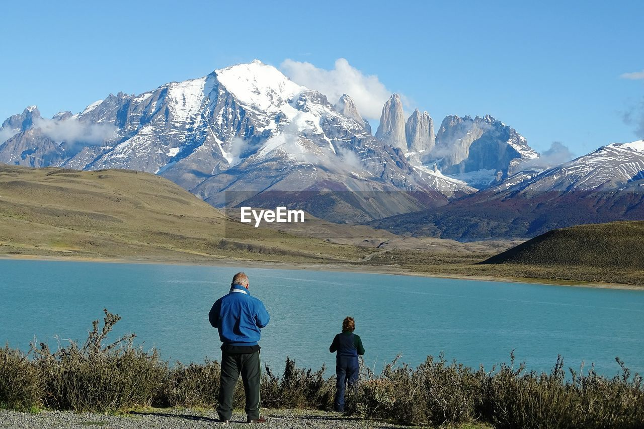 Man And Boy Standing At Lakeshore Against Snowcapped Mountains