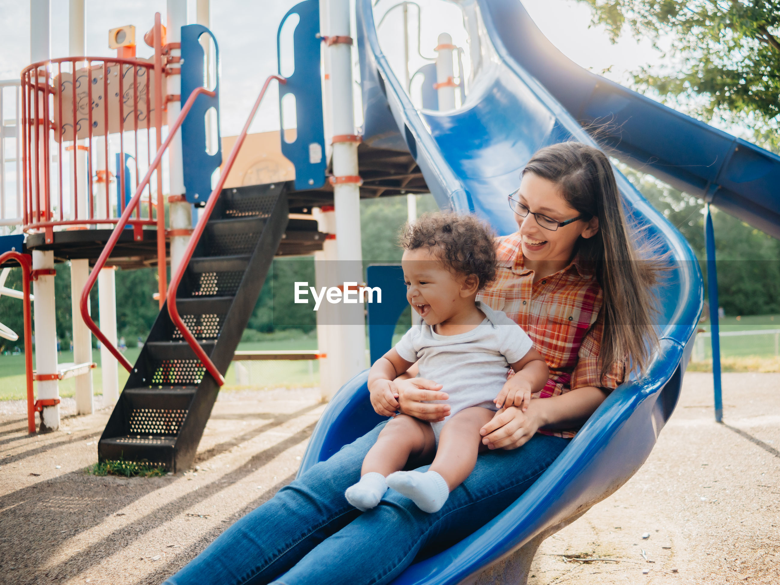 Smiling mother with cute kid sitting on slide at park