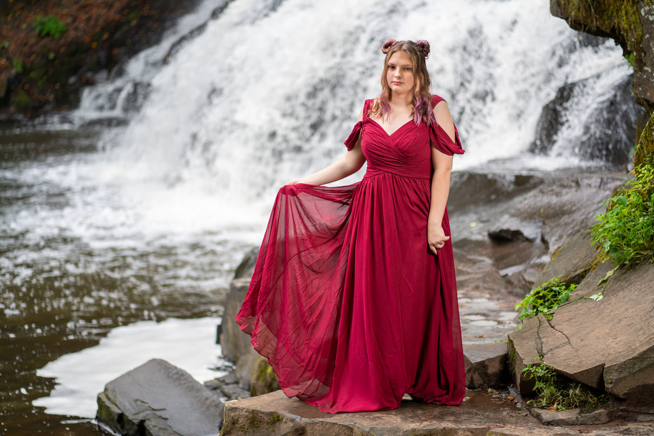 water, red, one person, clothing, full length, young adult, real people, waterfall, motion, dress, nature, lifestyles, standing, young women, fashion, flowing, women, beautiful woman, flowing water, outdoors