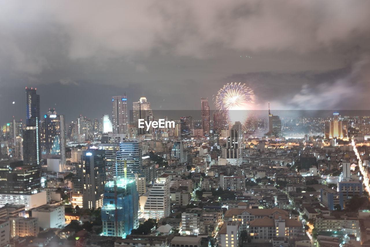 Firework Exploding Over Illuminated Cityscape Against Sky
