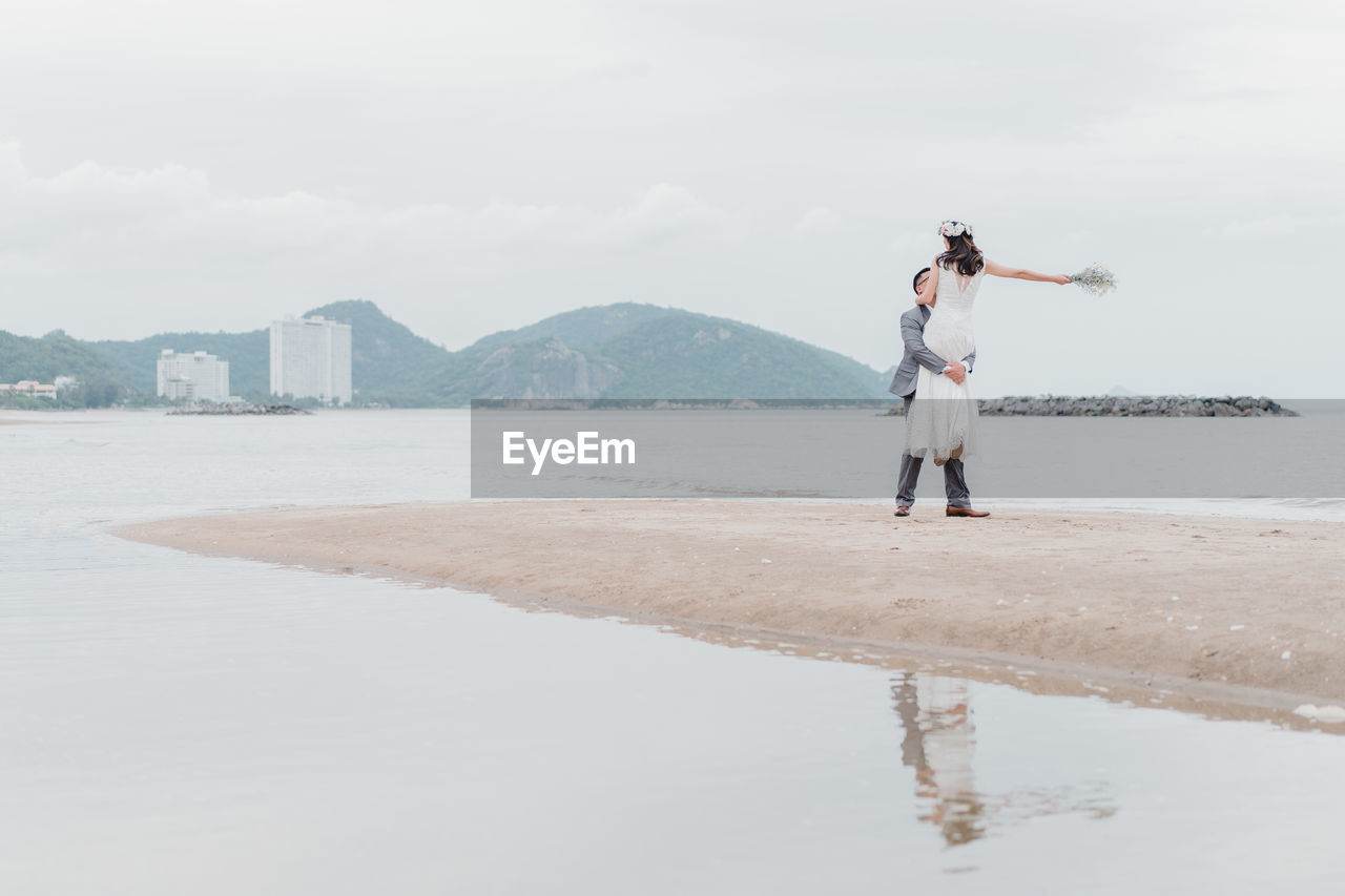 Newlywed couple standing on beach against sky