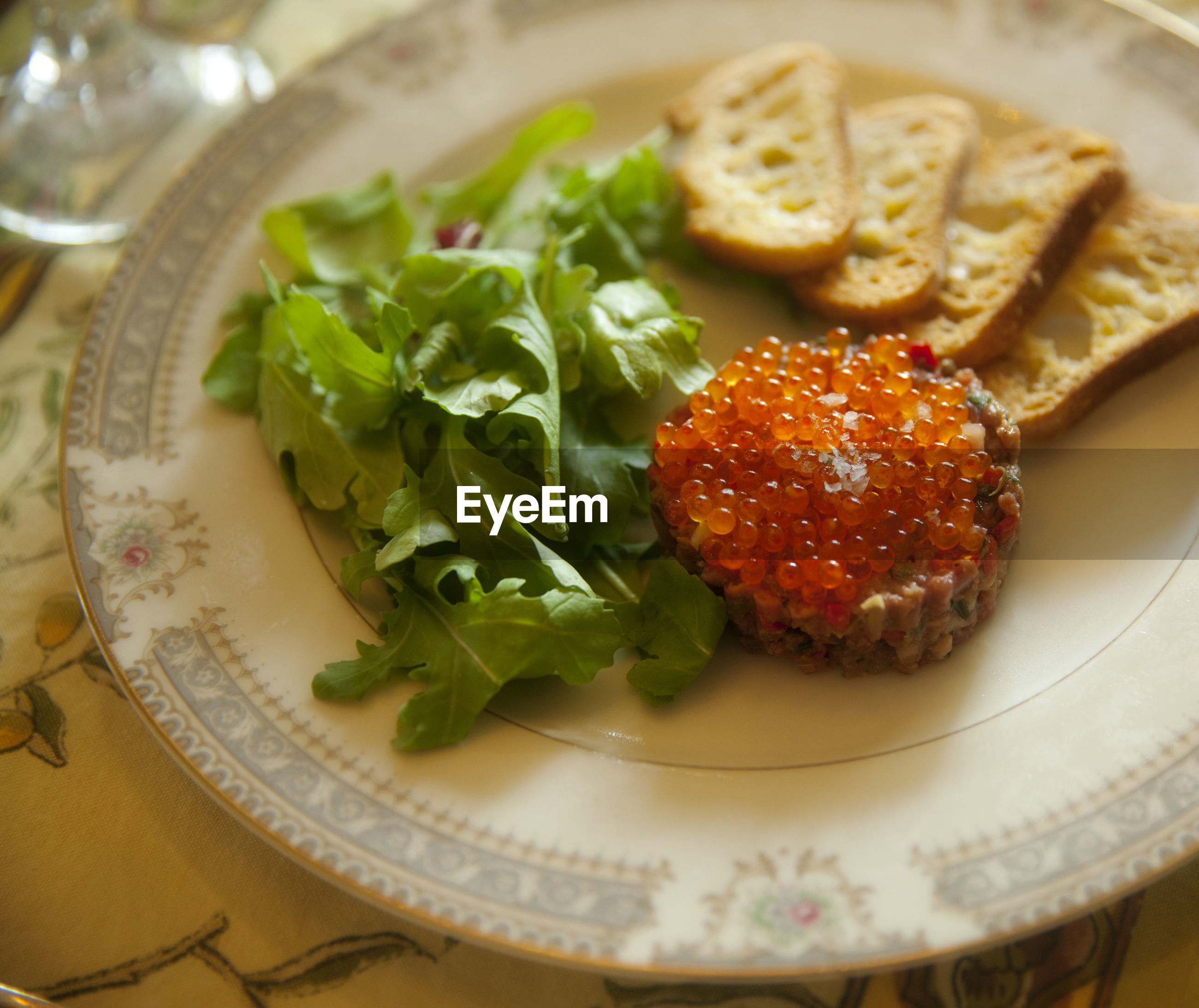 Close-up of steak tartare with rusk and arugula in plate
