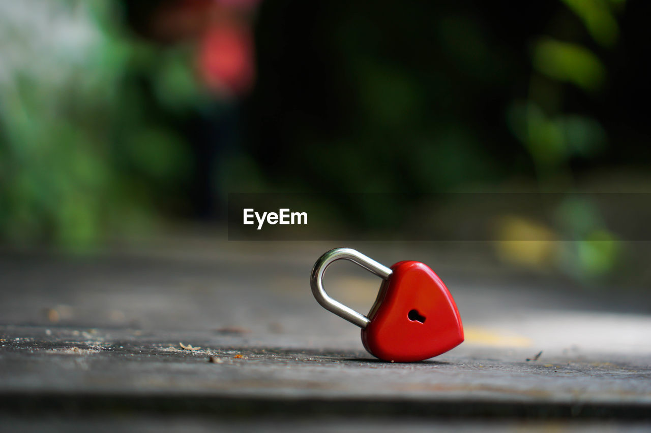 red, selective focus, close-up, day, no people, metal, single object, security, still life, focus on foreground, wood - material, lock, table, outdoors, nature, safety, representation, shape, heart shape, protection, surface level, personal accessory