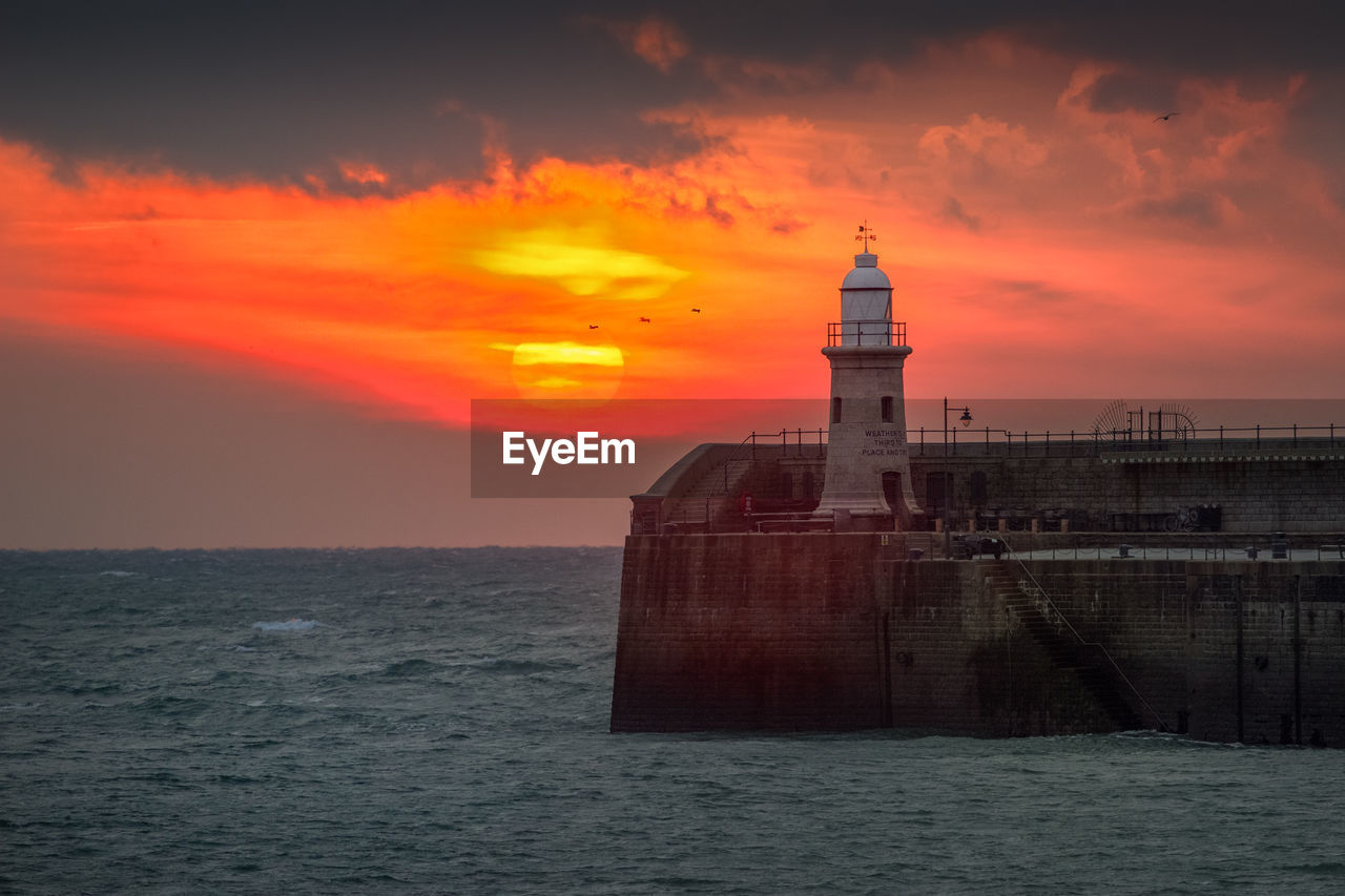 sky, sunset, built structure, sea, architecture, water, orange color, building exterior, waterfront, cloud - sky, tower, building, guidance, lighthouse, beauty in nature, no people, scenics - nature, protection, security, horizon over water, outdoors