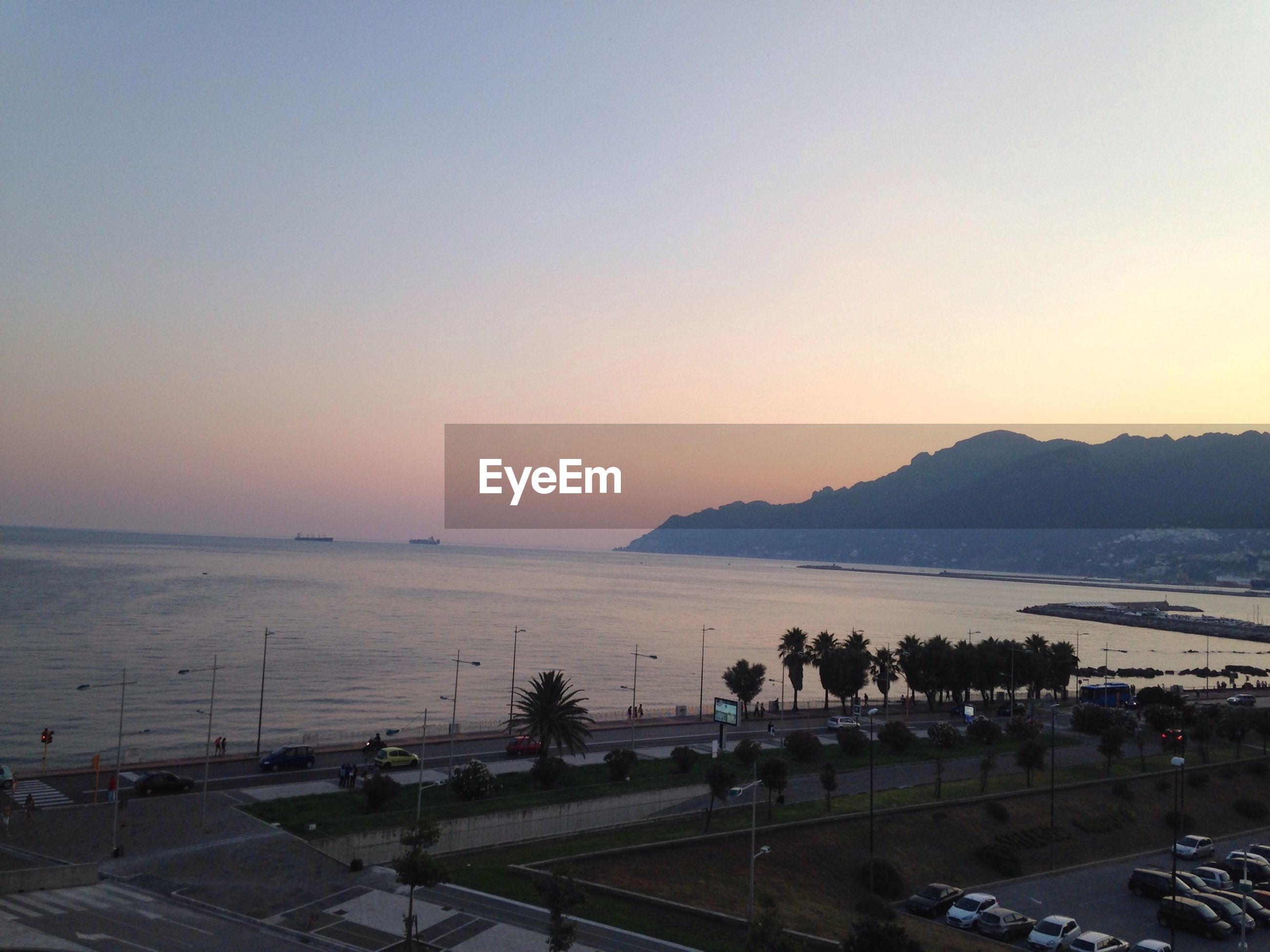 Scenic view of sea by mountain against clear sky at sunset