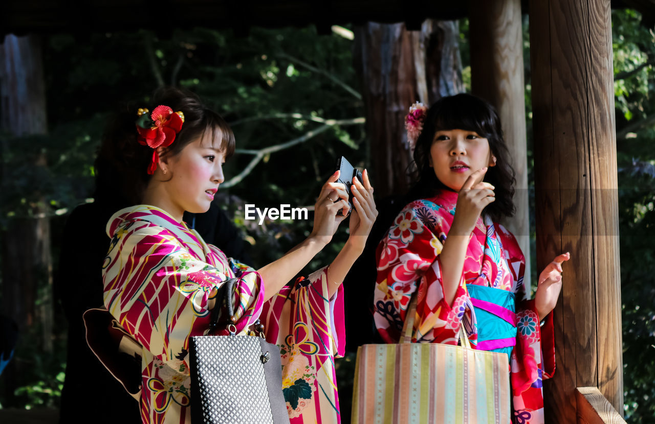 holding, fashion, young adult, real people, outdoors, two people, lifestyles, leisure activity, young women, portable information device, mobile phone, beautiful woman, casual clothing, wireless technology, smiling, day, togetherness, friendship, portrait, happiness, human hand